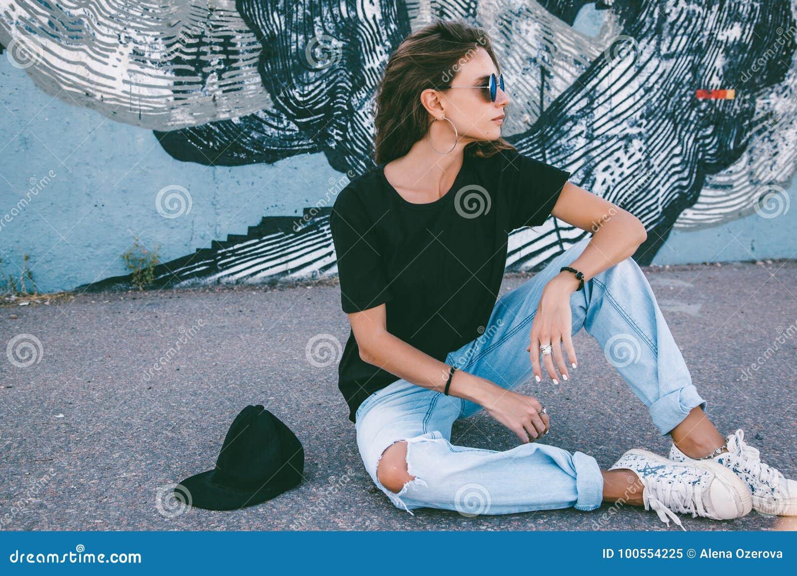 T-shirt modèle et lunettes de soleil simples de port posant au-dessus de la rue wal