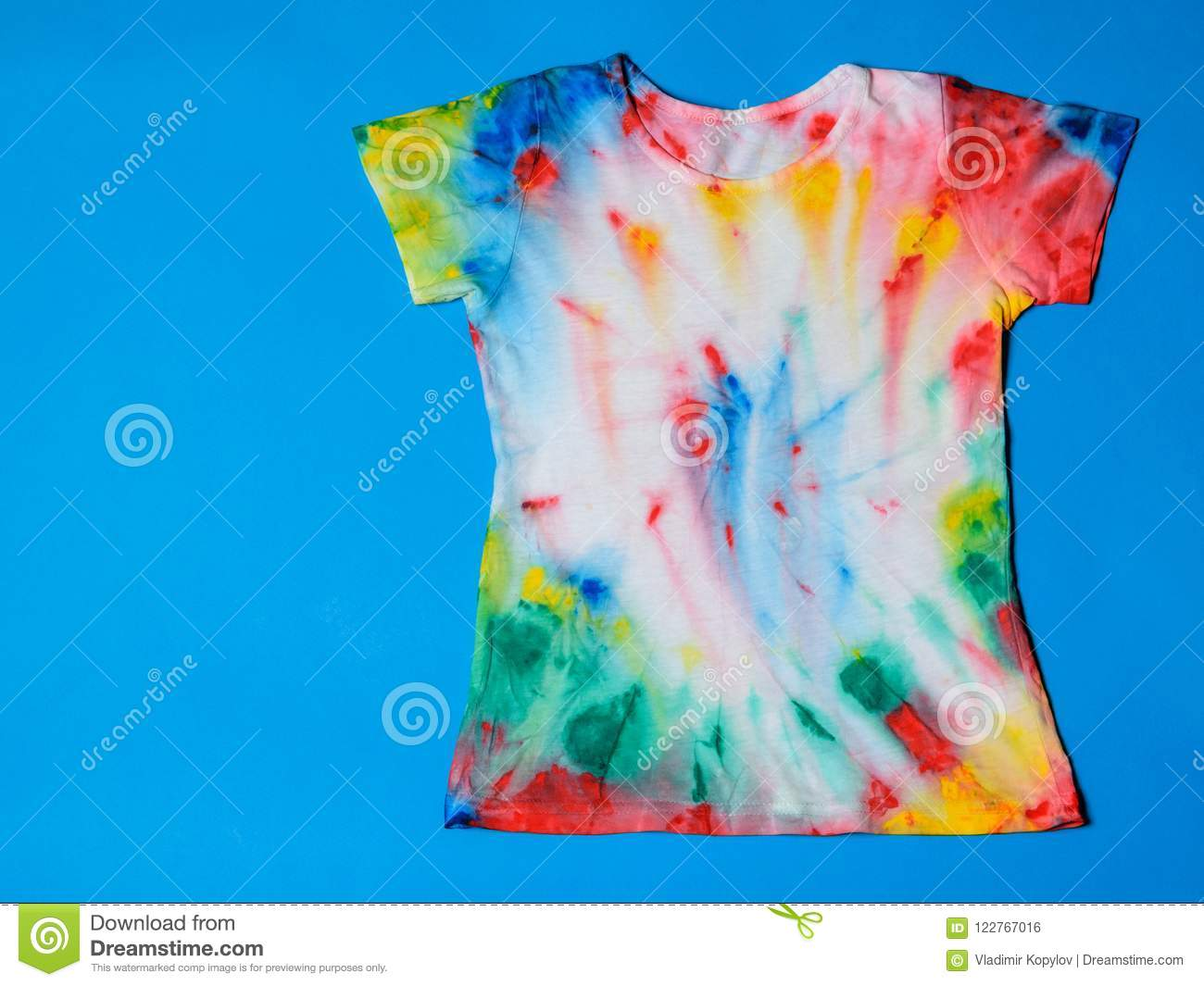1914a594 T-shirt painted in tie dye style on a blue background. Flat lay. Place for  text.