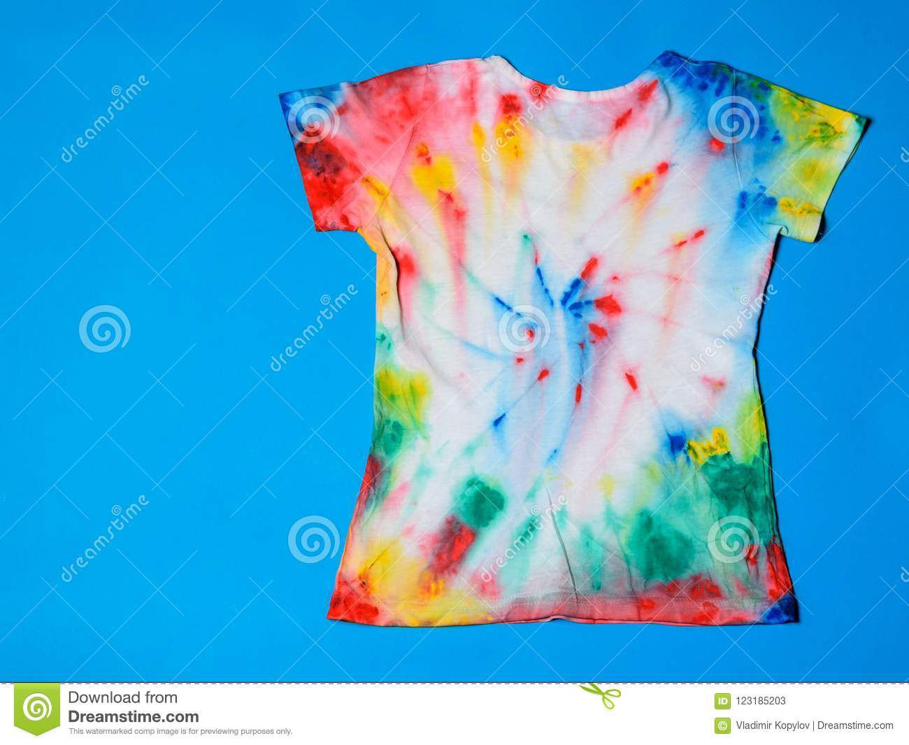 09404cd6 T-shirt Painted In Tie Dye Style On A Blue Background. Flat Lay. The ...