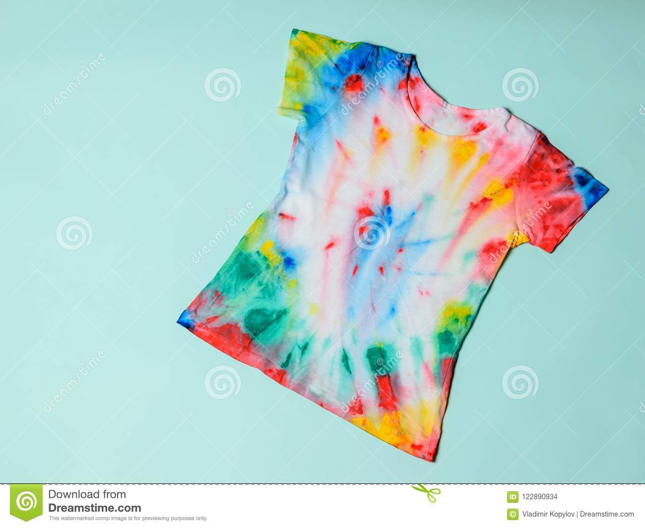 b8f1ade9 T-shirt painted in tie dye style on a blue pastel background. Flat lay