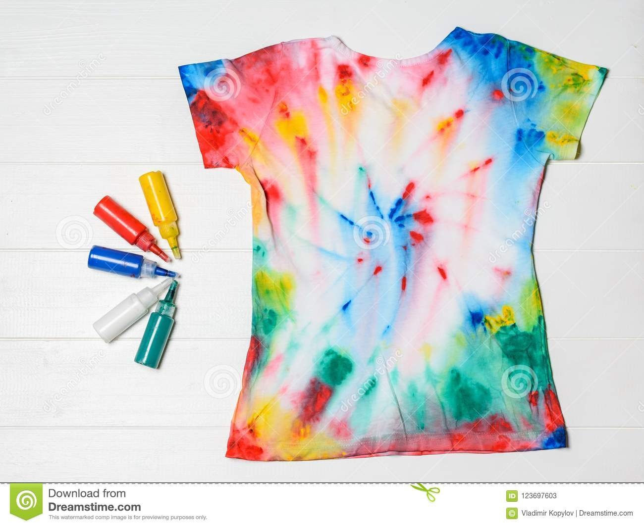 1474dc0f T-shirt painted in tie dye style with colors on a white wooden table. Flat  lay.