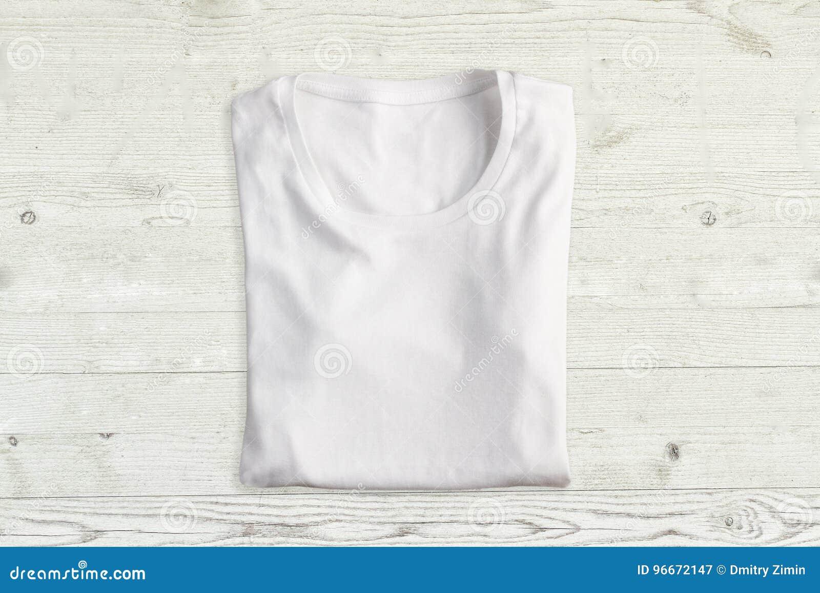 T-shirt plié par blanc sur la texture en bois