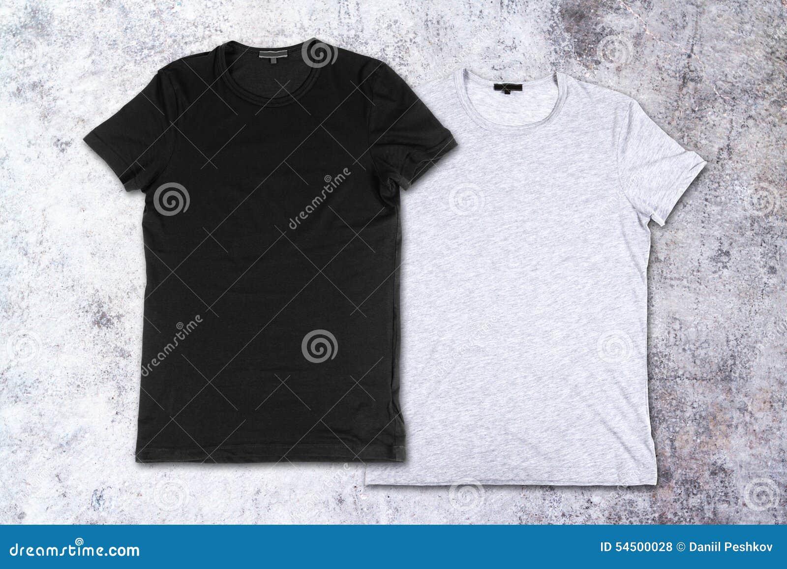 T-shirts vides sur le fond du mur en béton