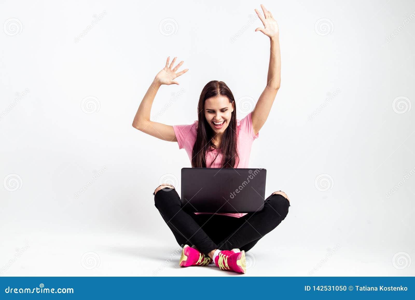T-skjortan och jeans för lycklig nätt flicka sitter rymmer den iklädda rosa på golvet med bärbara datorn och hennes händer upp på