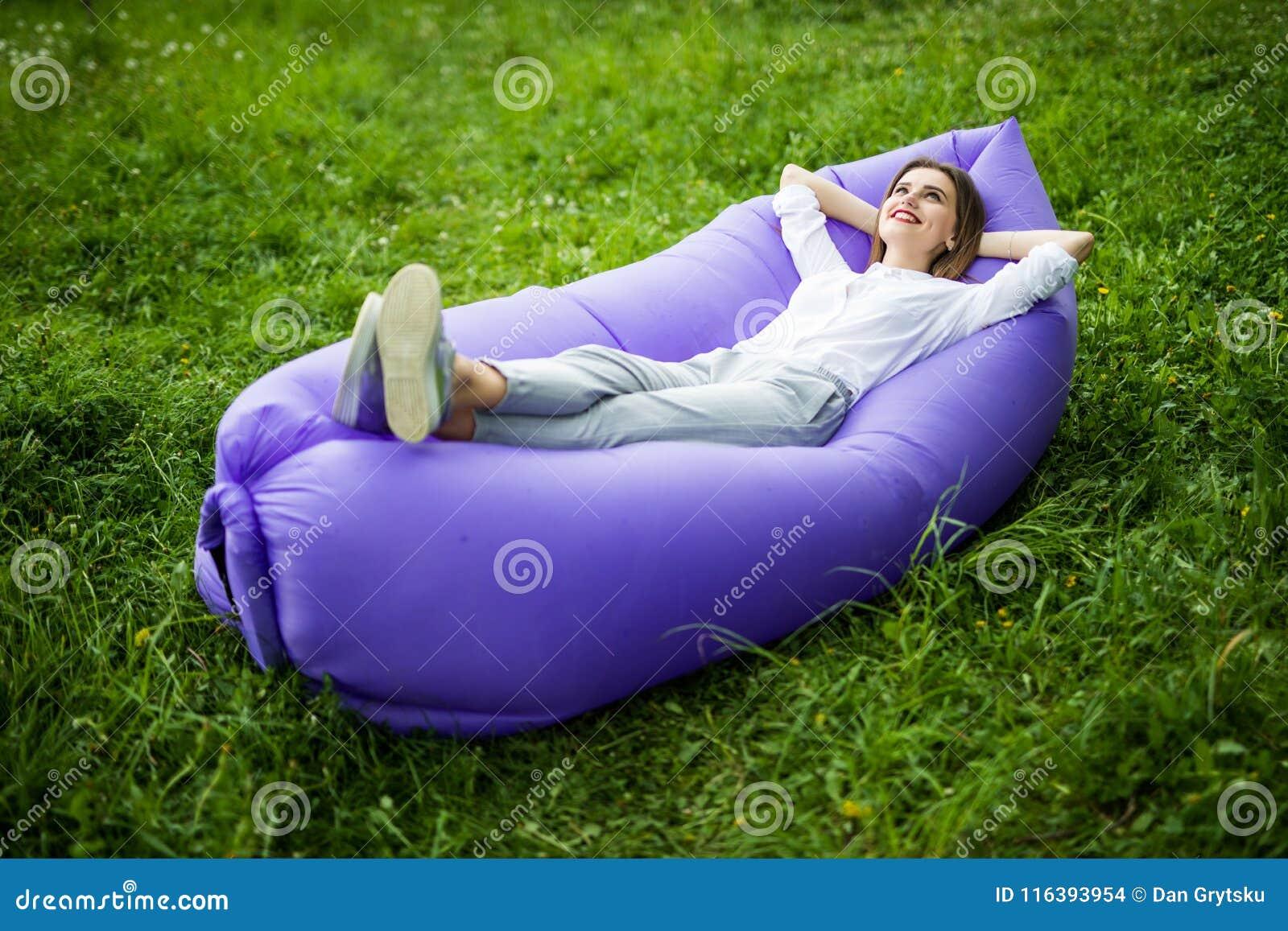 Ta ett avbrott Den nätta unga kvinnan som ligger på uppblåsbar soffalamzac, medan vila på gräs, parkerar in på solen