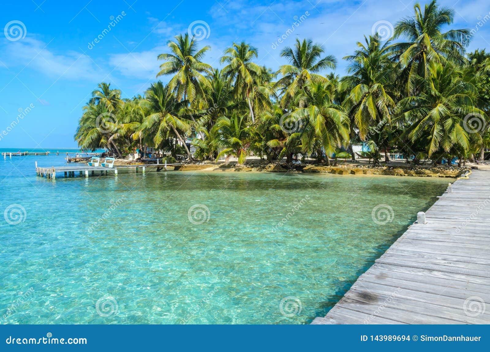 Tabaco Caye - relaj?ndose en el embarcadero de madera en la peque?a isla tropical en la barrera de arrecifes con la playa del par