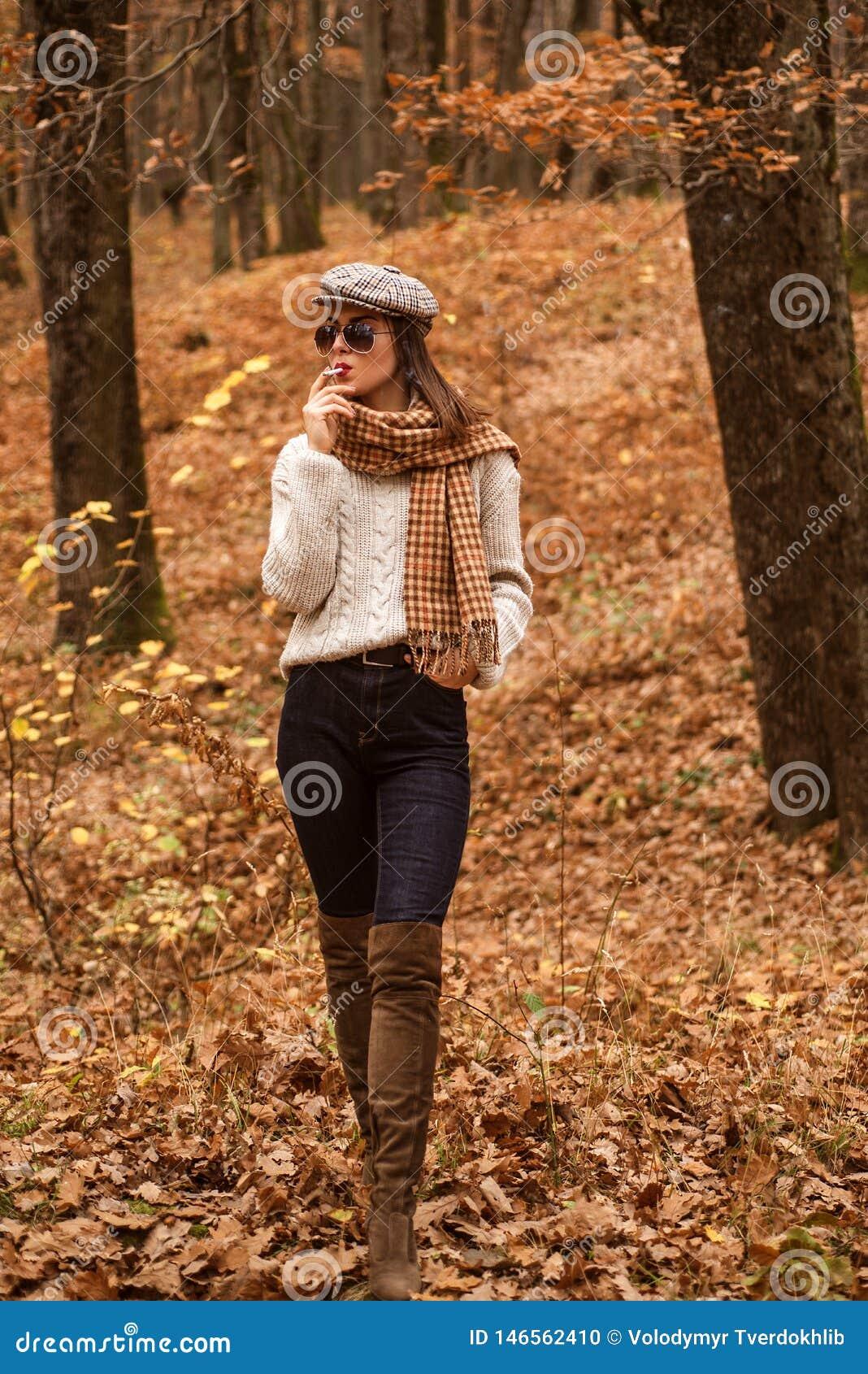 Tabagisme de détente La femme ont plaisir seul à fumer Fumeur seul L automne est ici Jolie femme dans le tabagisme de chapeau et