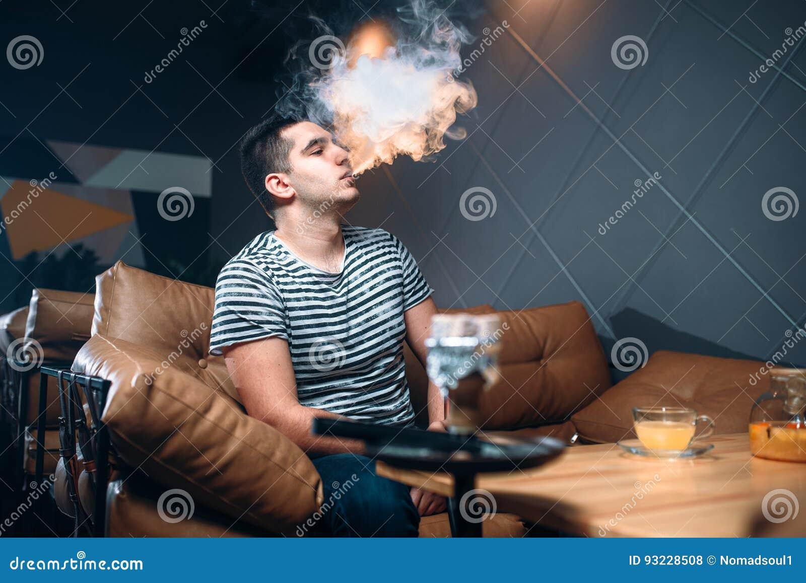 Tabagisme et relaxation de jeune homme à la barre de narguilé