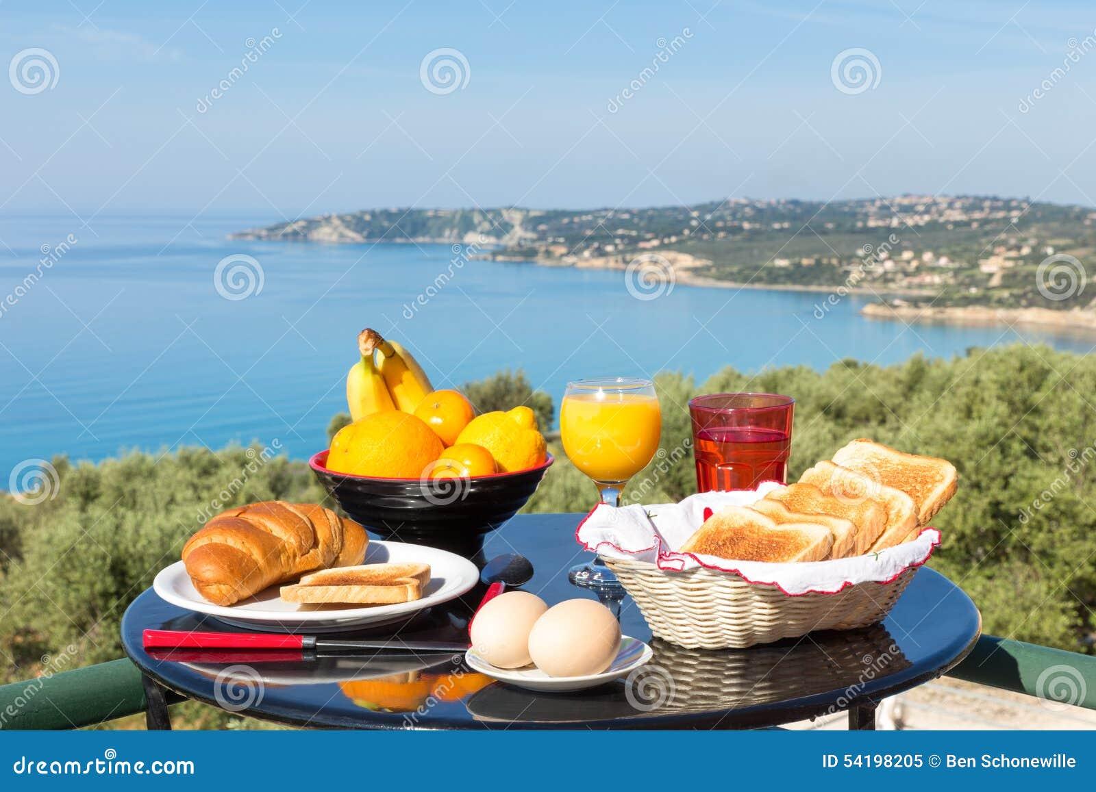 Tabela com alimento e bebidas na frente do mar e da praia azuis