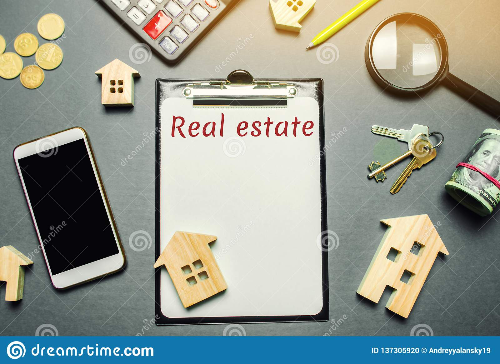 Tabela com casas de madeira, calculadora, moedas, lupa com os bens imobiliários da palavra Comprando e vendendo bens imobiliários