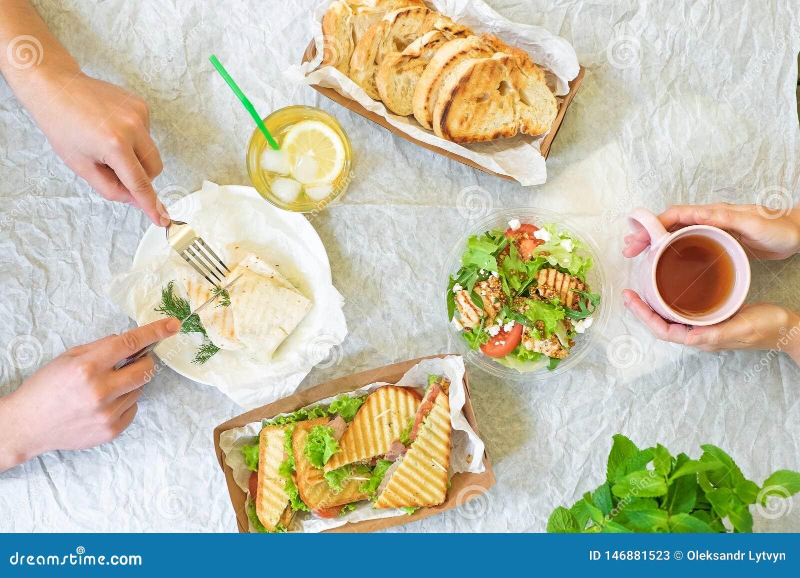 Tabela com mãos, vista superior dos sanduíches da salada de Caesar, do bruschetta, do presunto e do tomate de cima de