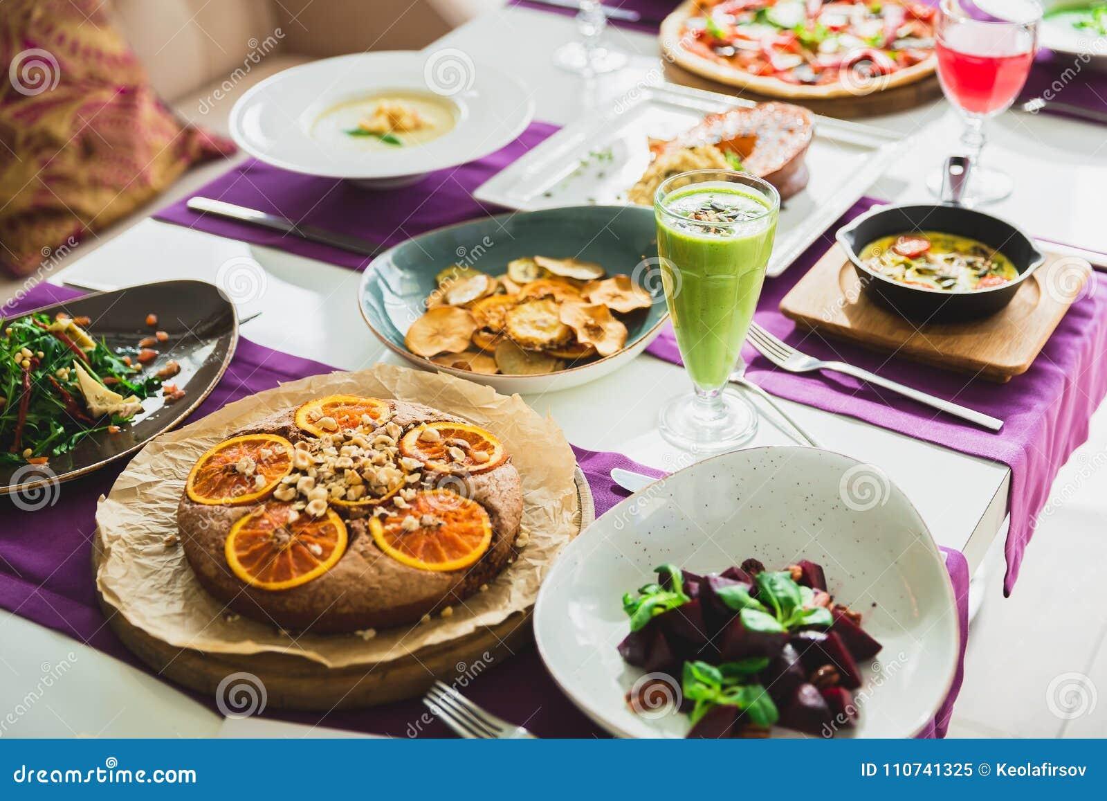 Tabela com pratos de vegetariano - pizza, saladas, torta e bebidas Alimento no restaurante