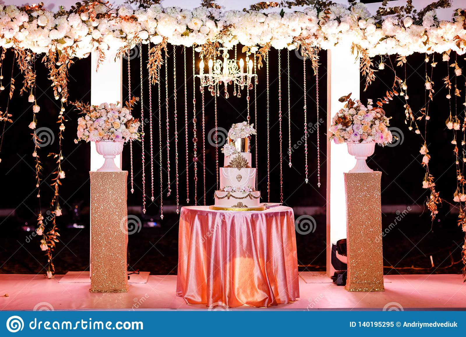 Tabela com um bolo de casamento, velas, luz e flores Decoração do casamento
