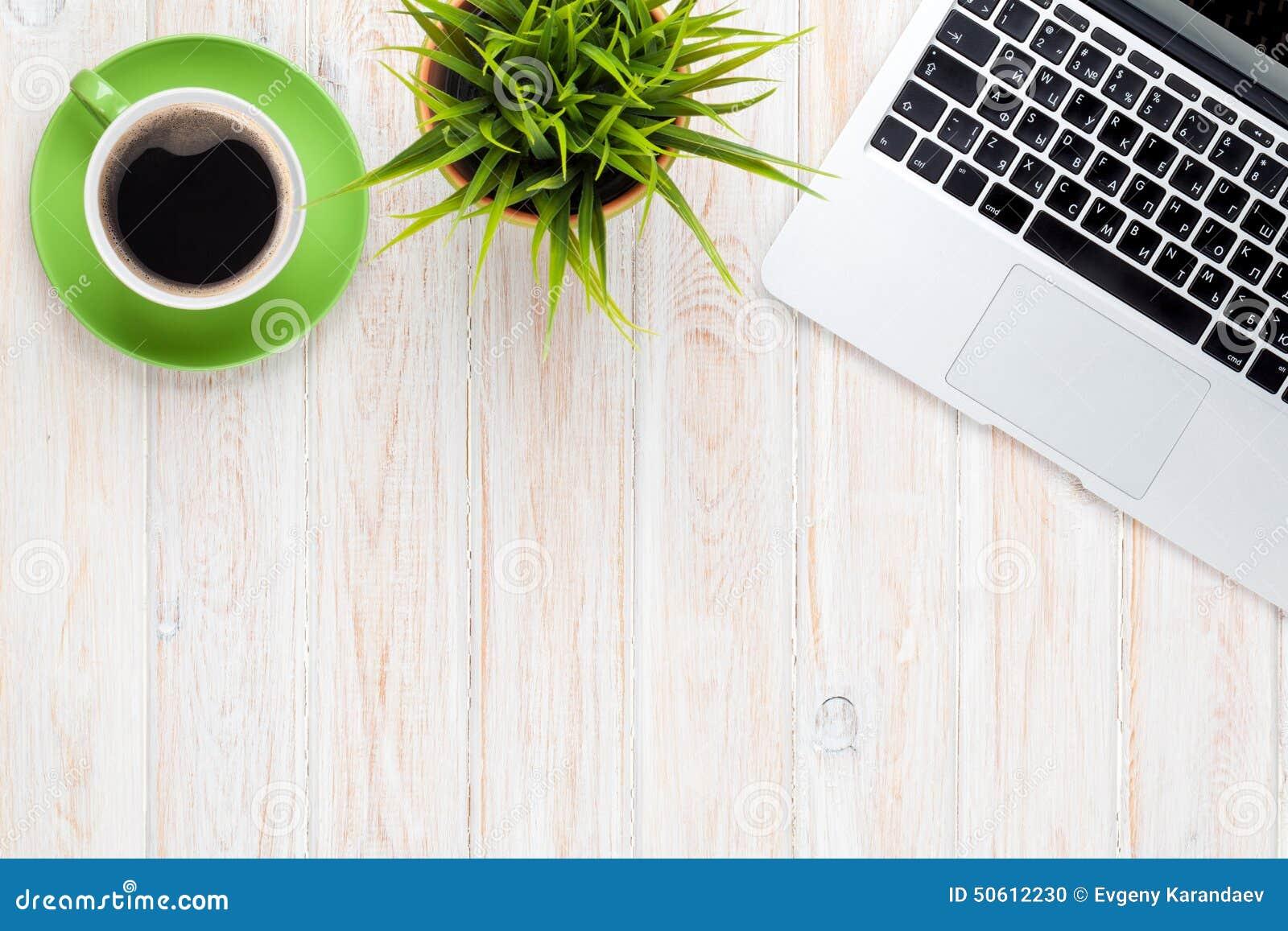 Tabela da mesa de escritório com o copo e a flor de café do laptop