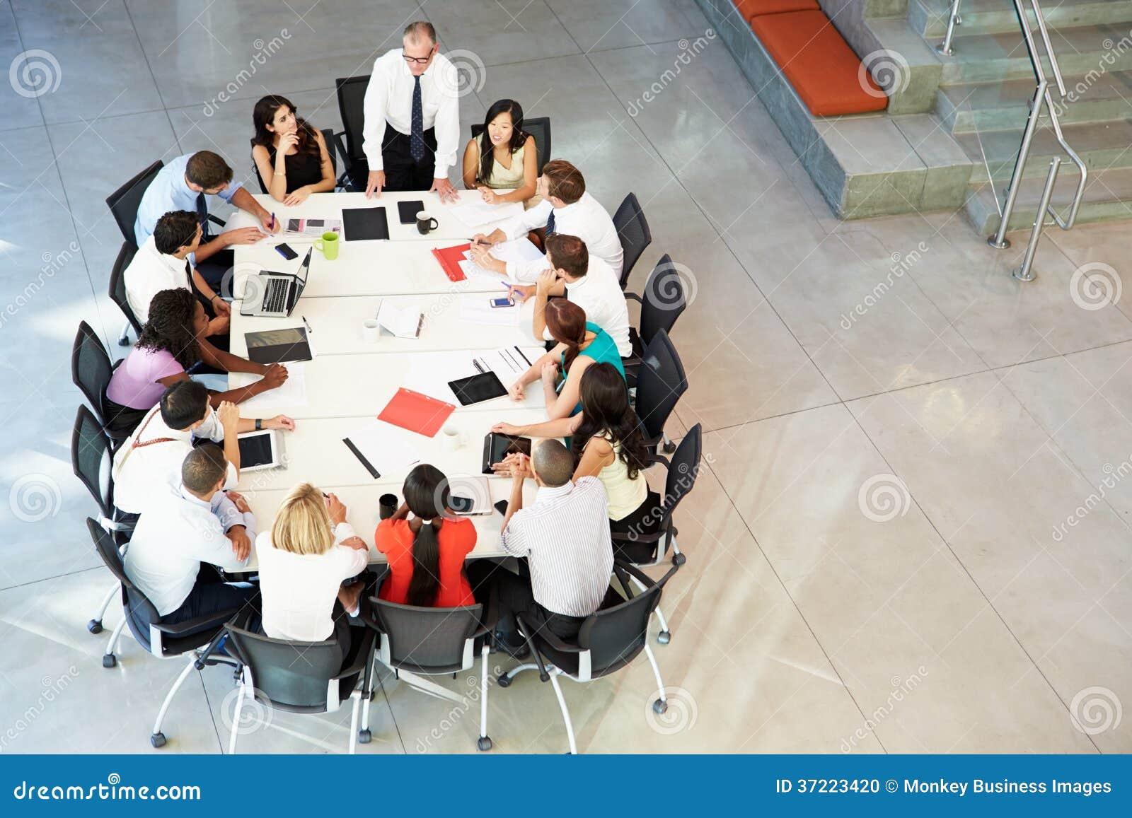 Tabela da sala de reuniões de Addressing Meeting Around do homem de negócios