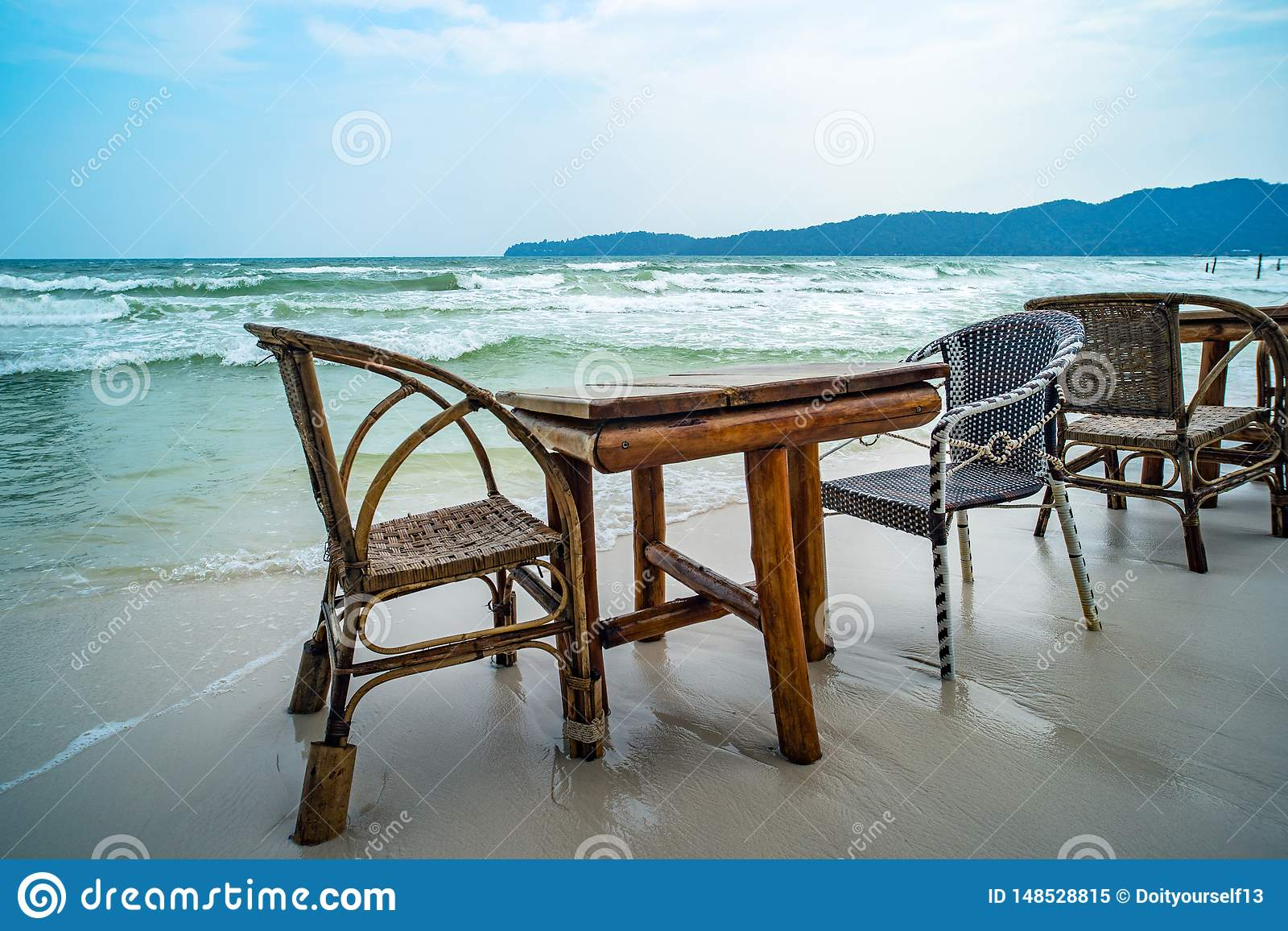 Tabela de bambu e cadeiras de madeira no caf? vazio ao lado da ?gua do mar na praia tropical Fim acima Ilha Koh Phangan