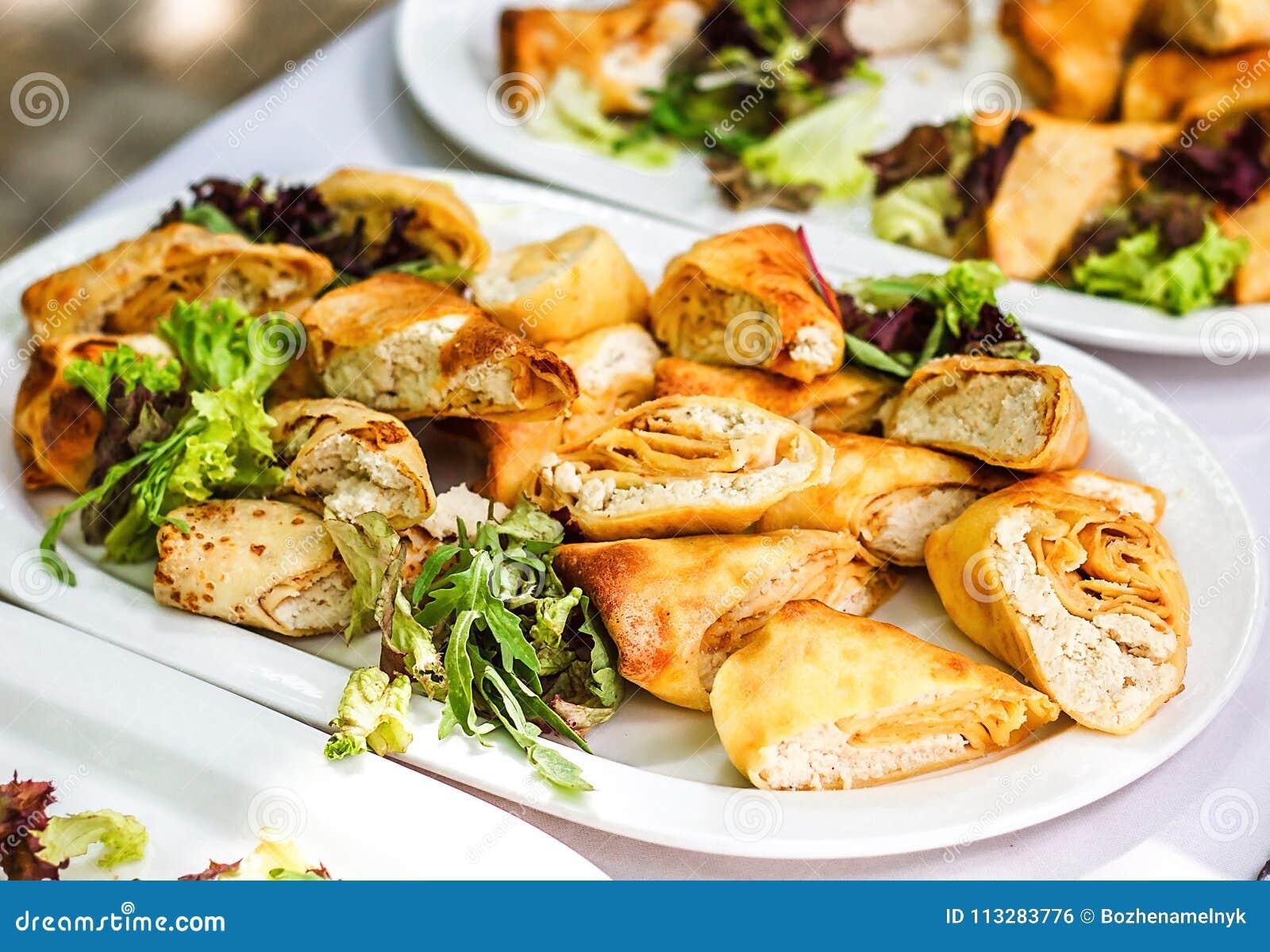Tabela de banquete de abastecimento belamente decorada com os petiscos do alimento e os aperitivos diferentes com sanduíche, panq