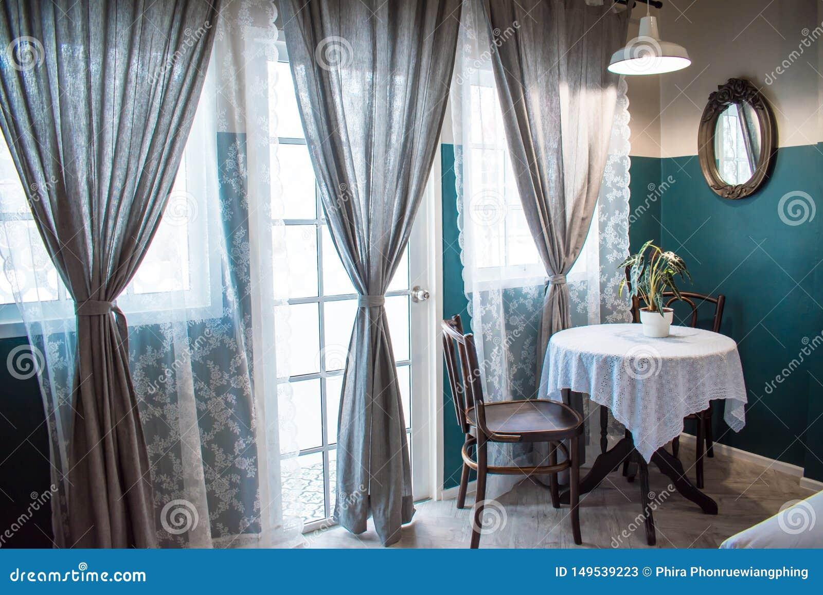 Tabela de chá ajustada com os potenciômetros da planta ao lado das grandes janelas e das grandes cortinas cinzentas com filtro da