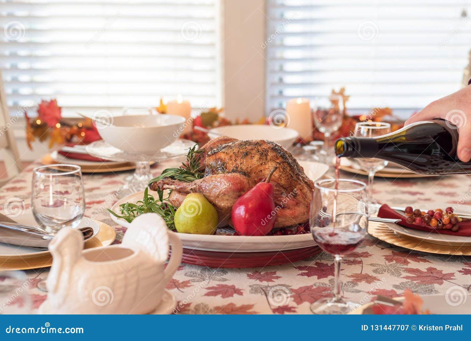 Tabela de jantar do feriado com peru roasted, vinho tinto de derramamento do homem no primeiro plano