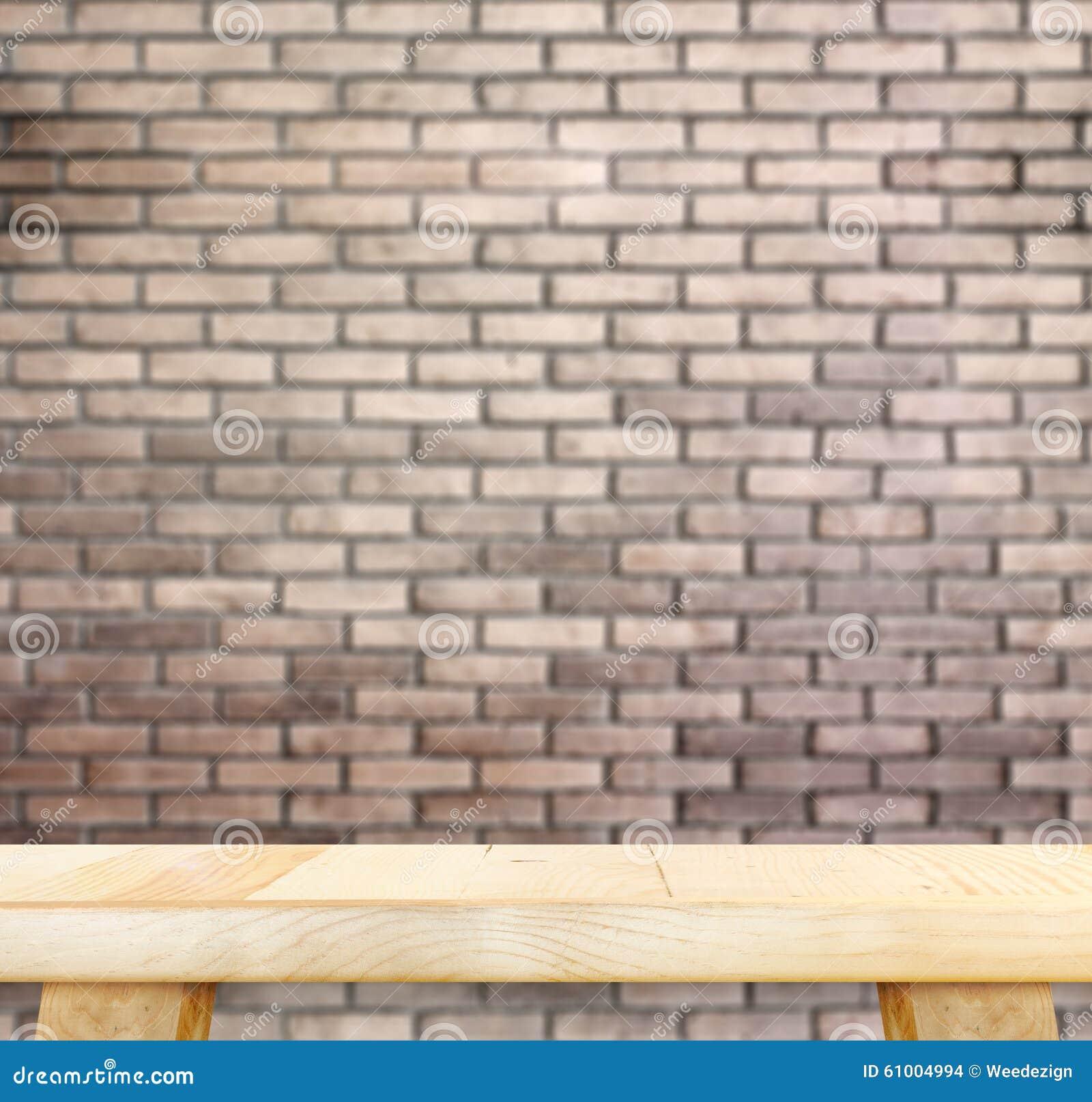 Tabela de madeira clara vazia e parede de tijolo vermelho do borrão no fundo, Moc