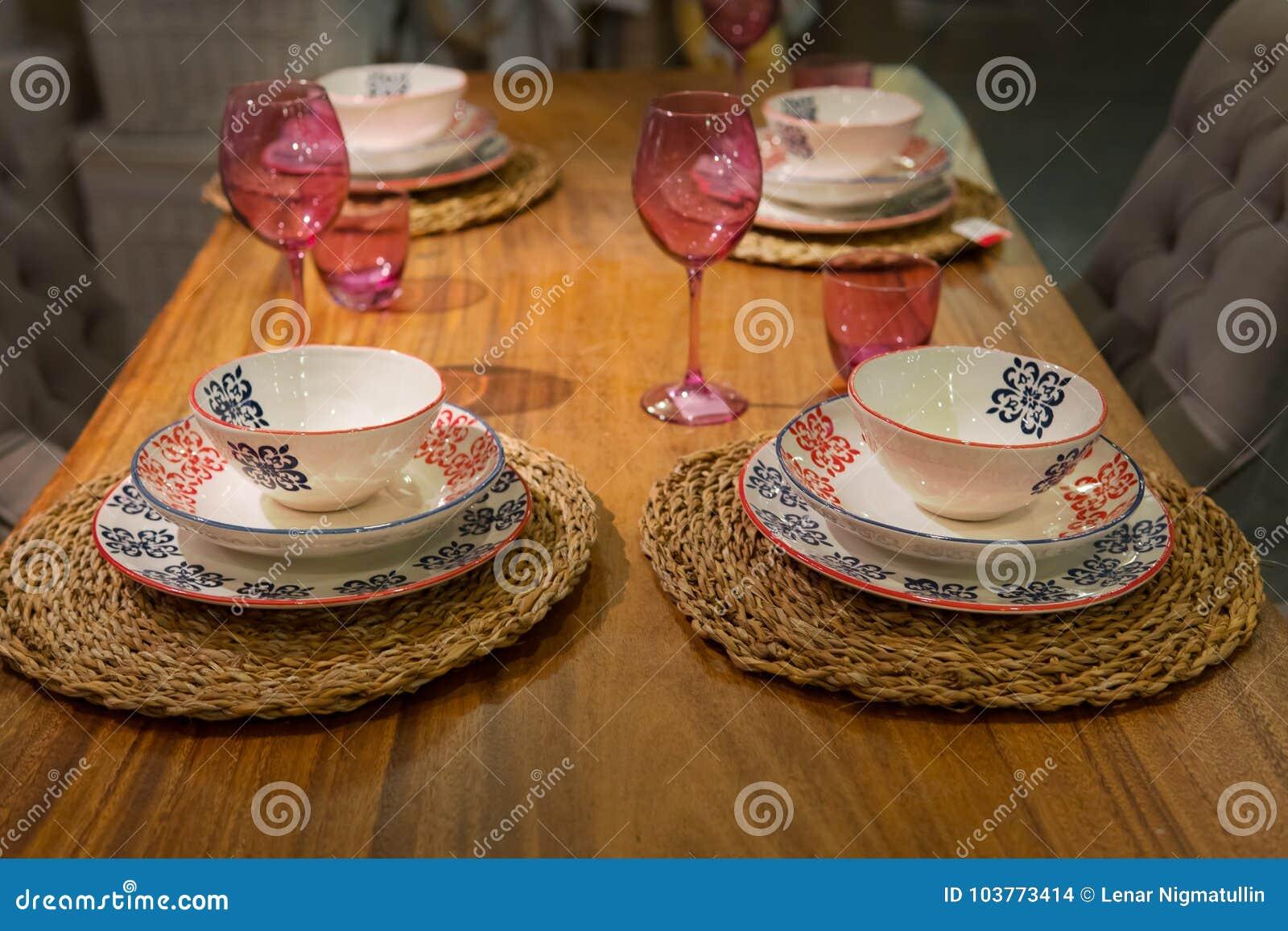Tabela de madeira com vidros de vinho e os pratos cerâmicos