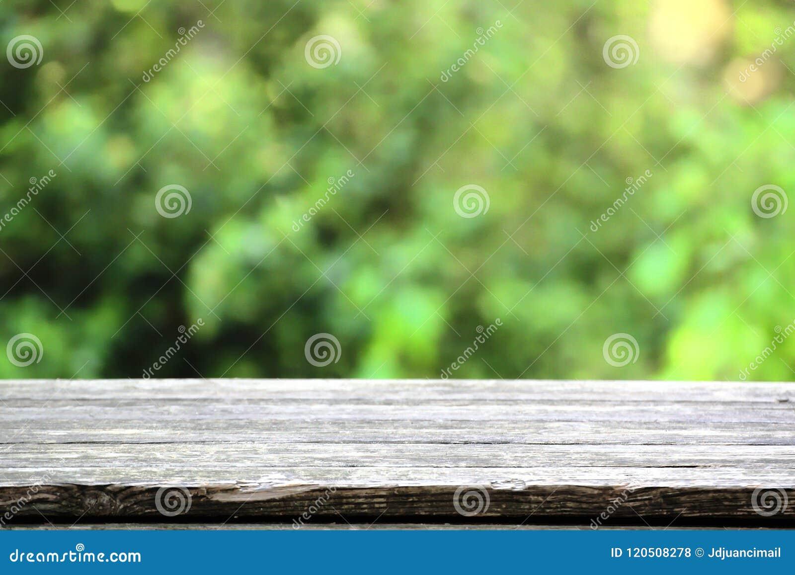 Tabela de madeira natural em um ambiente rústico contra um fundo verde blured espaço vazio da cópia