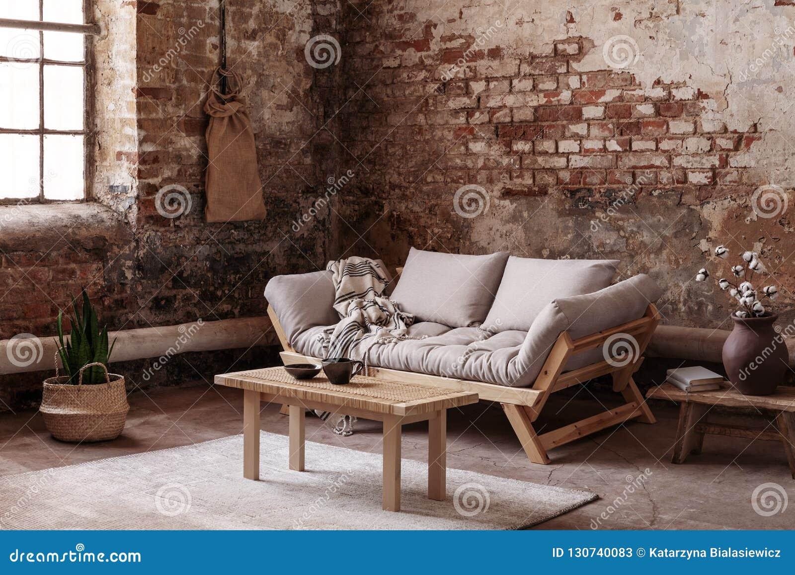 Tabela de madeira no tapete na frente do sofá bege no interior do apartamento no estilo do sabi do wabi com a parede de tijolo ve