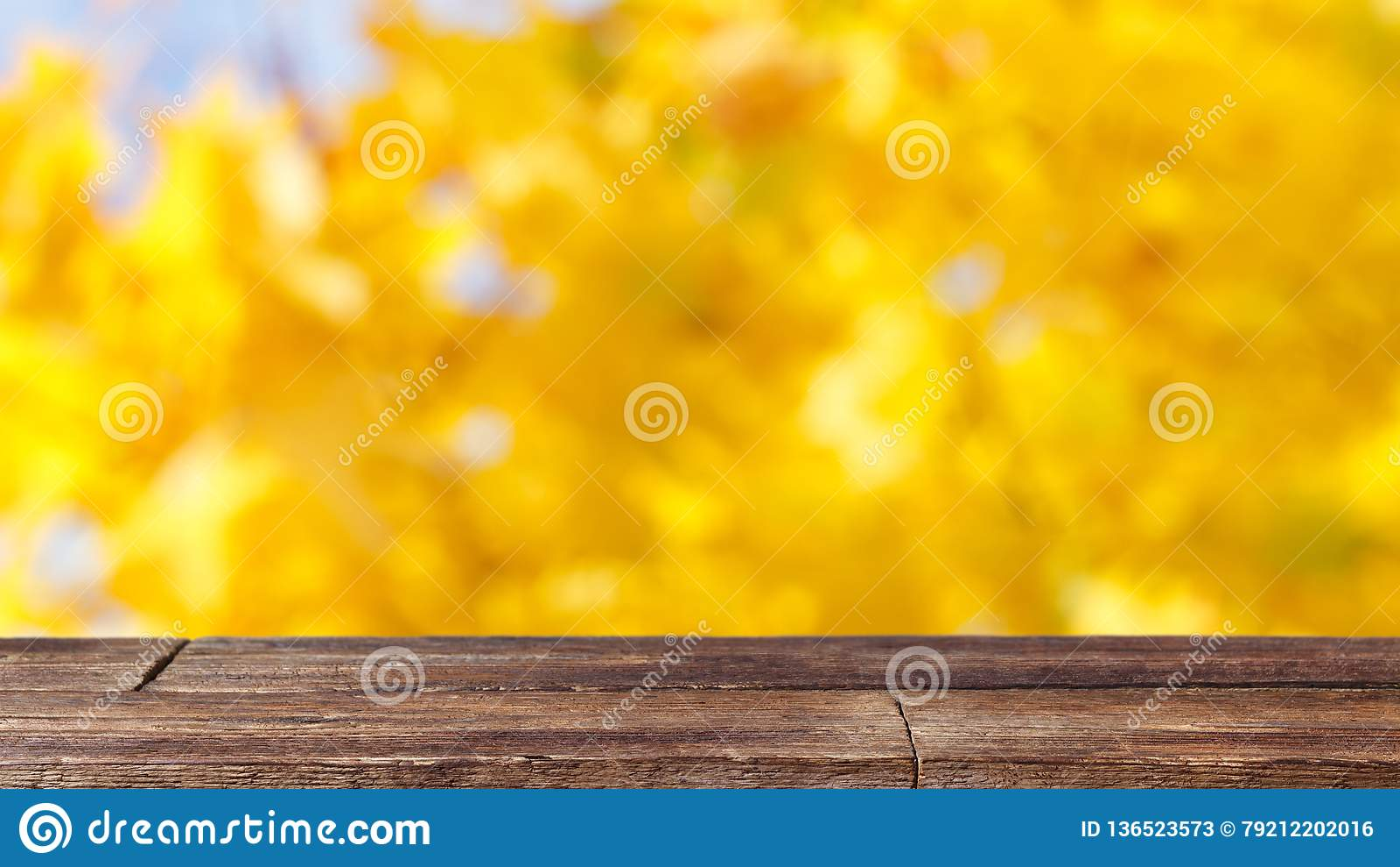 Tabela de madeira rústica no fundo abstrato do bokeh amarelo
