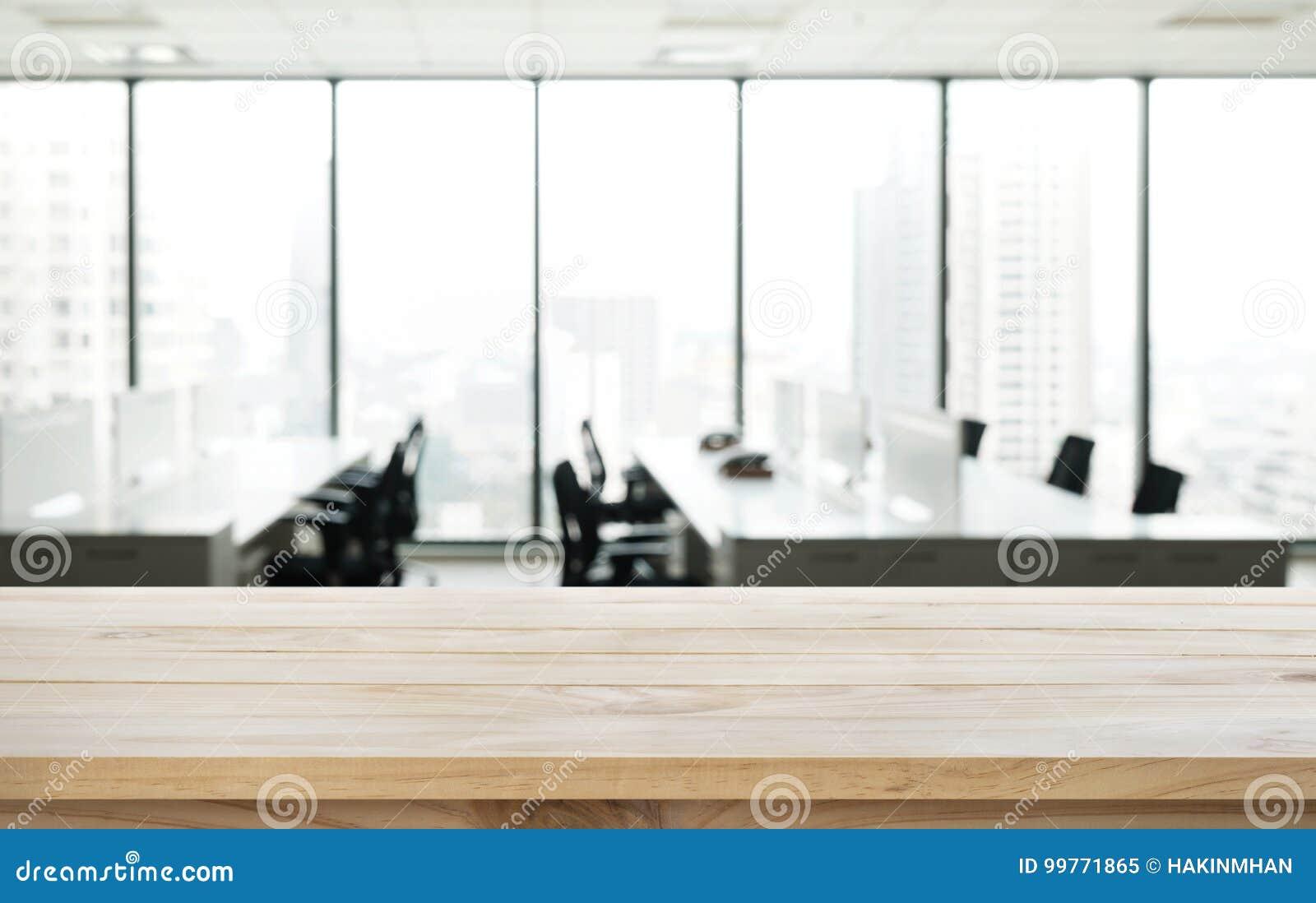 Tabela de madeira vazia com opinião do escritório da sala do borrão e da cidade da janela