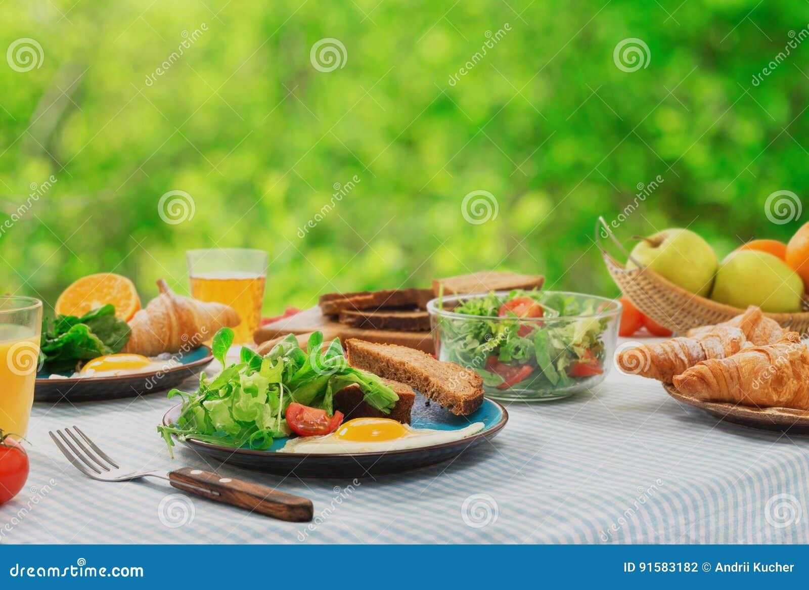 Tabela de pequeno almoço com alimento saudável ovos fritos, salada, croissant