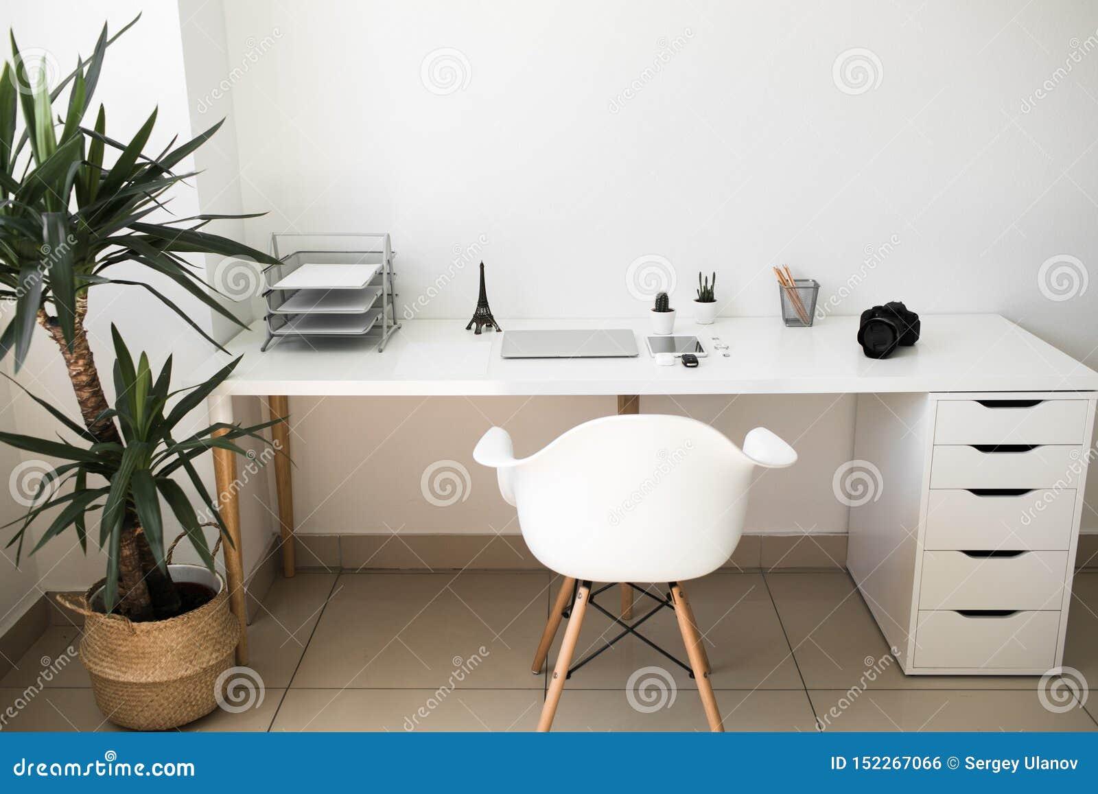 Tabela do escritório em que portátil, em café, em tabuleta, em câmera e em outros artigos