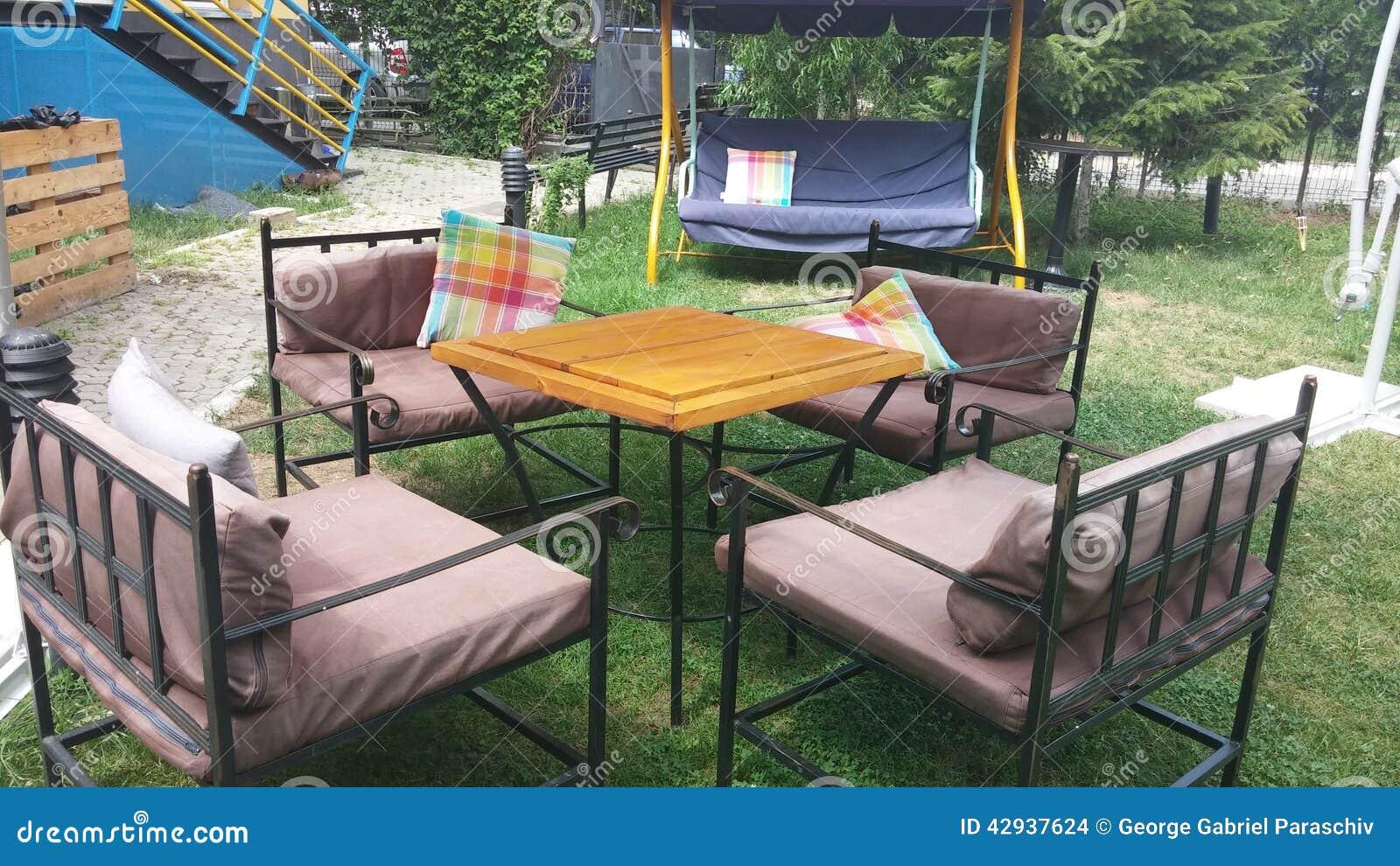 Jardim Com Cadeiras Do Ferro E Um Balanço Para O Abrandamento Foto de  #A46C27 1300x821