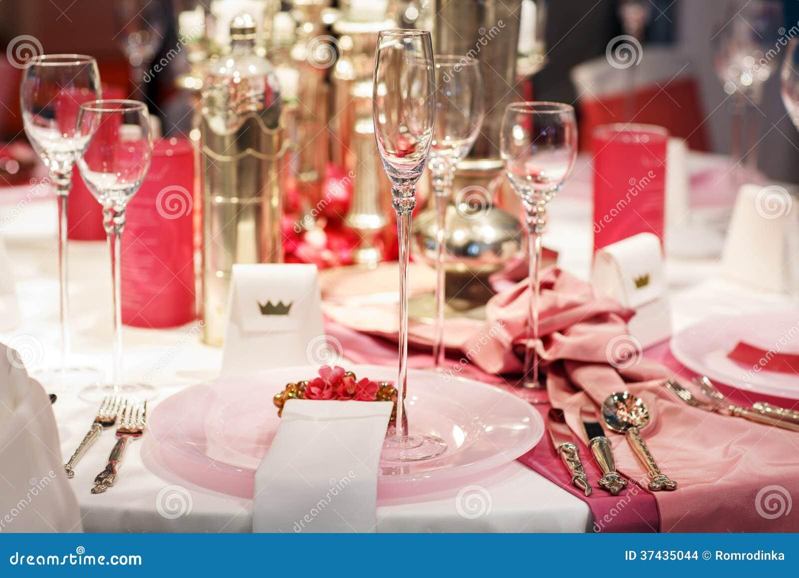 A tabela elegante ajustou-se em brandamente vermelho e cor-de-rosa para a peça do casamento ou do evento