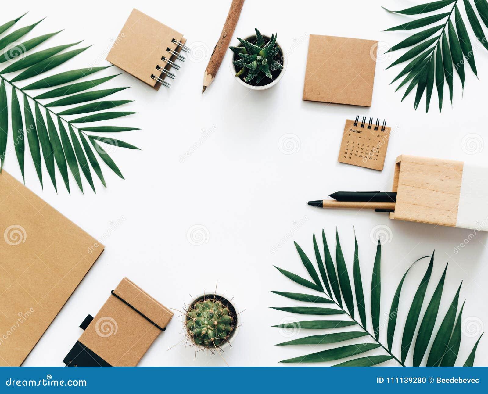 Tabela mínima da mesa de escritório com grupo, fontes e folhas de palmeira dos artigos de papelaria Vista superior
