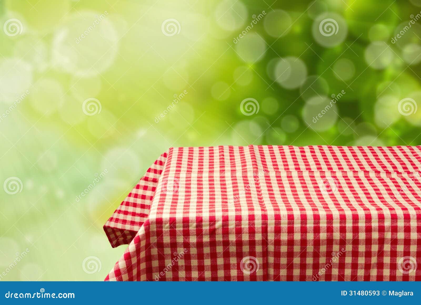 A tabela vazia com vermelho verificou a toalha de mesa sobre o fundo verde do bokeh.