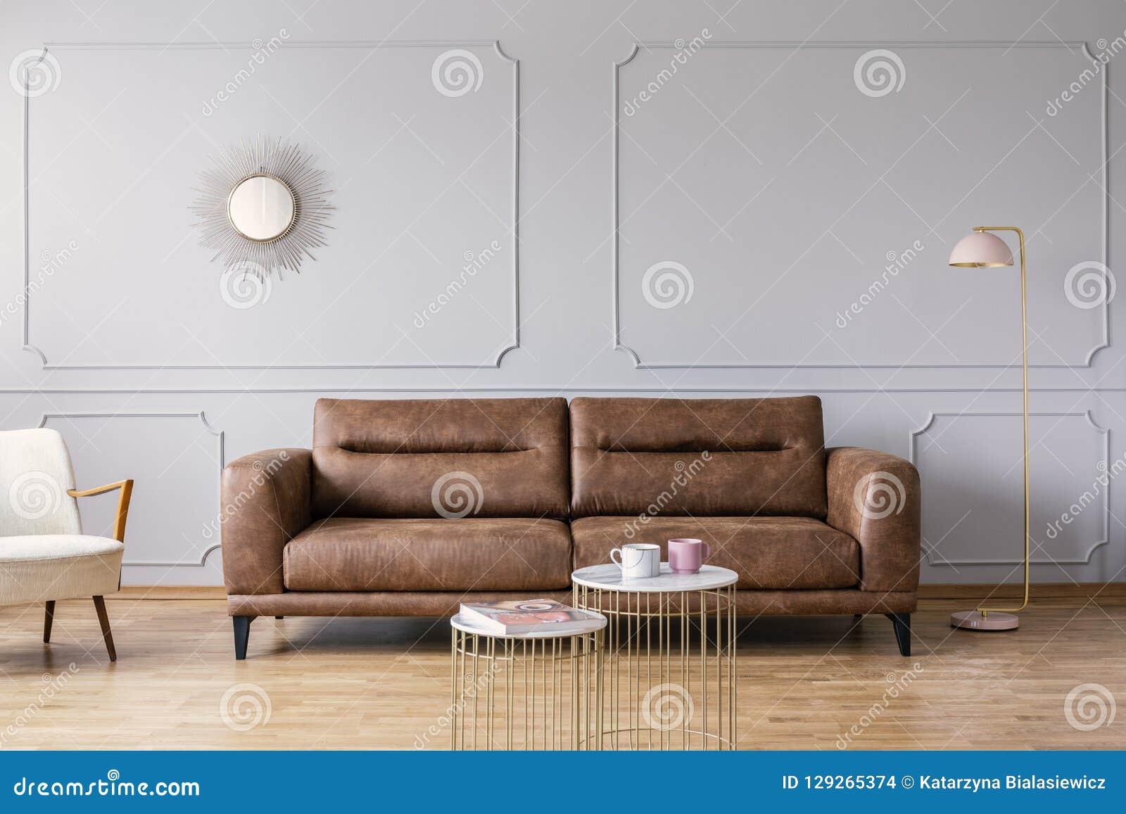 Tabelas do ouro na frente do sofá de couro no interior elegante cinzento da sala de visitas com espelho e lâmpada