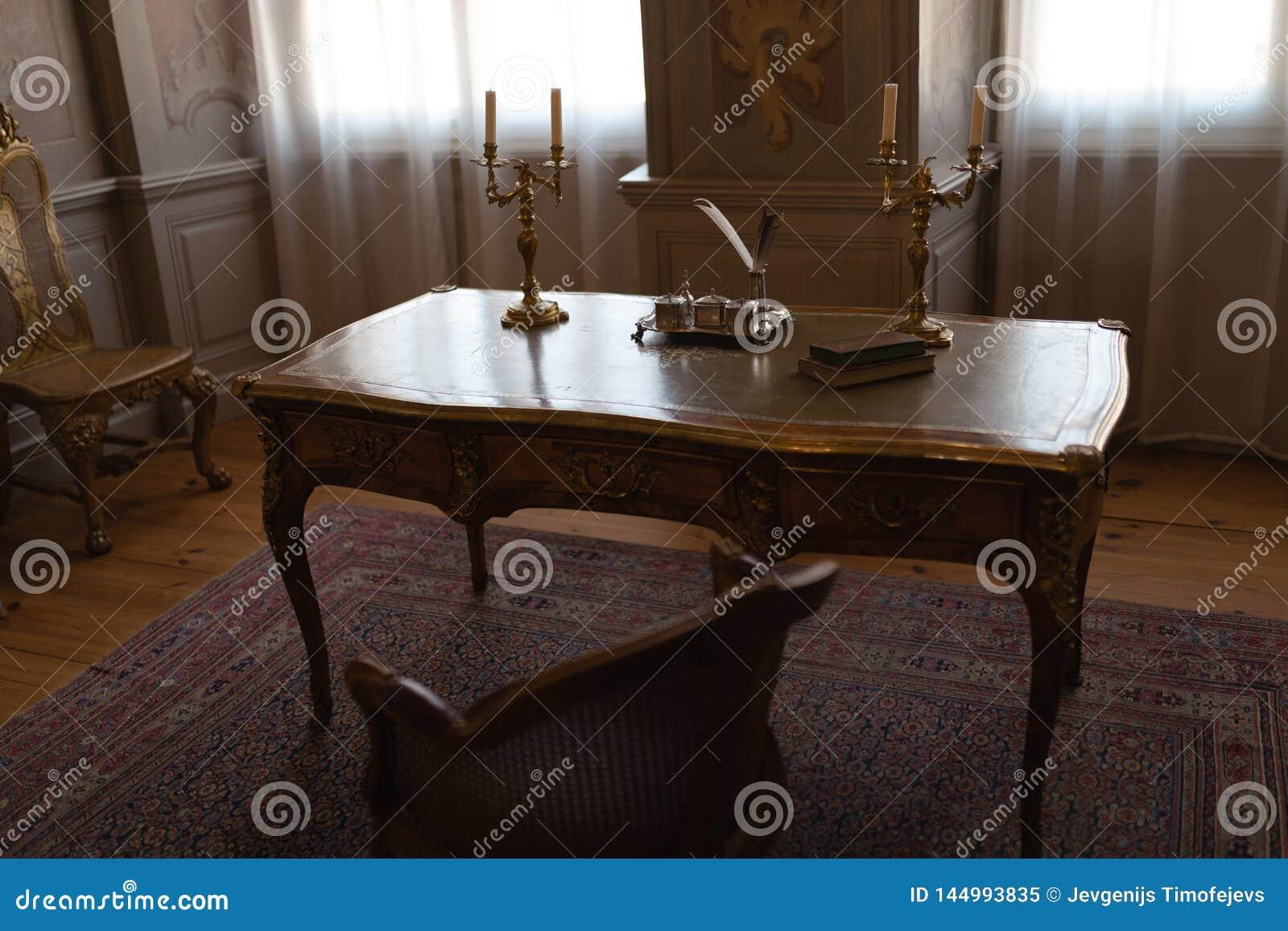 Tabell för kunglig slott i ett kabinett rum med stolar och penna och färgpulver