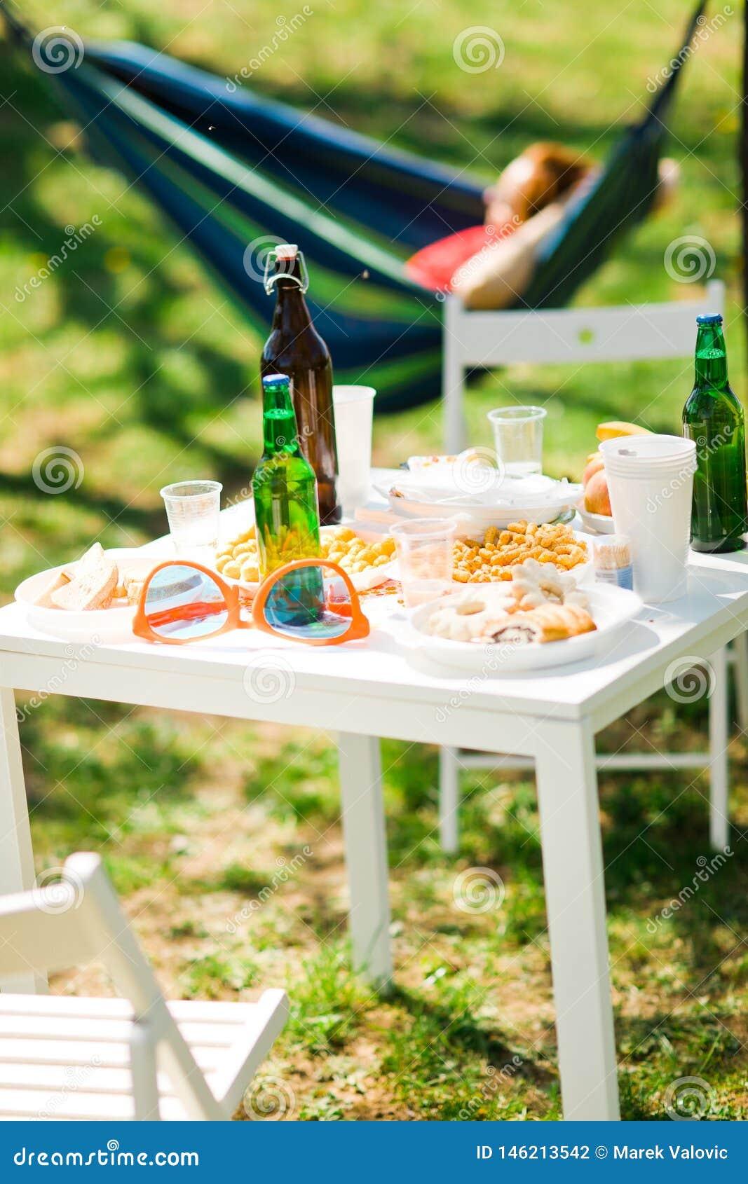 Tabell med flaskor av öl och mat på sommarträdgårdpartiet