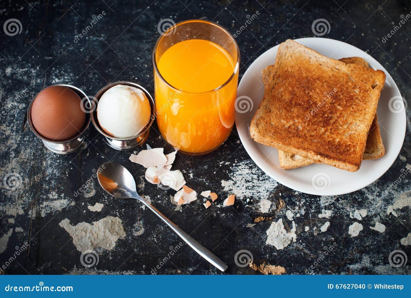 Tabella arancio di juice toasts spoon rustic shabby degli uova sode