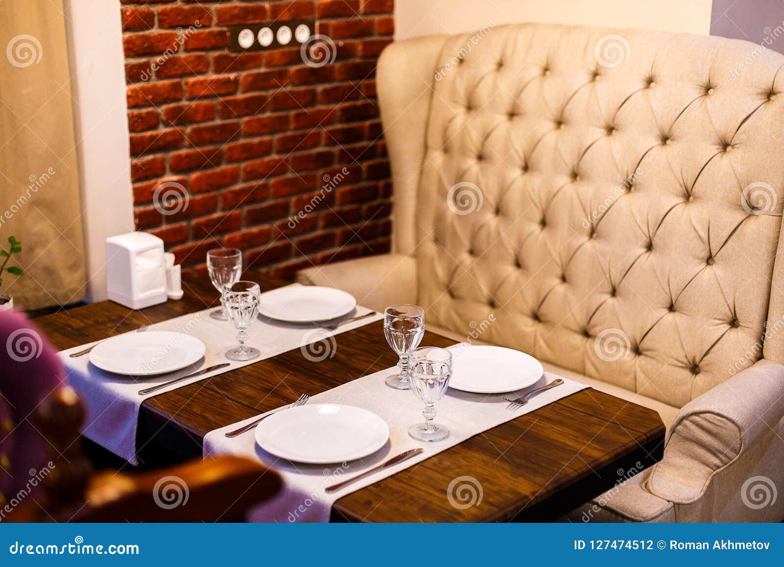 Tabelle in einem Café, dienend in einem Café, in einem beige Sofa der Weinlese, im Holztisch und in einer Backsteinmauer
