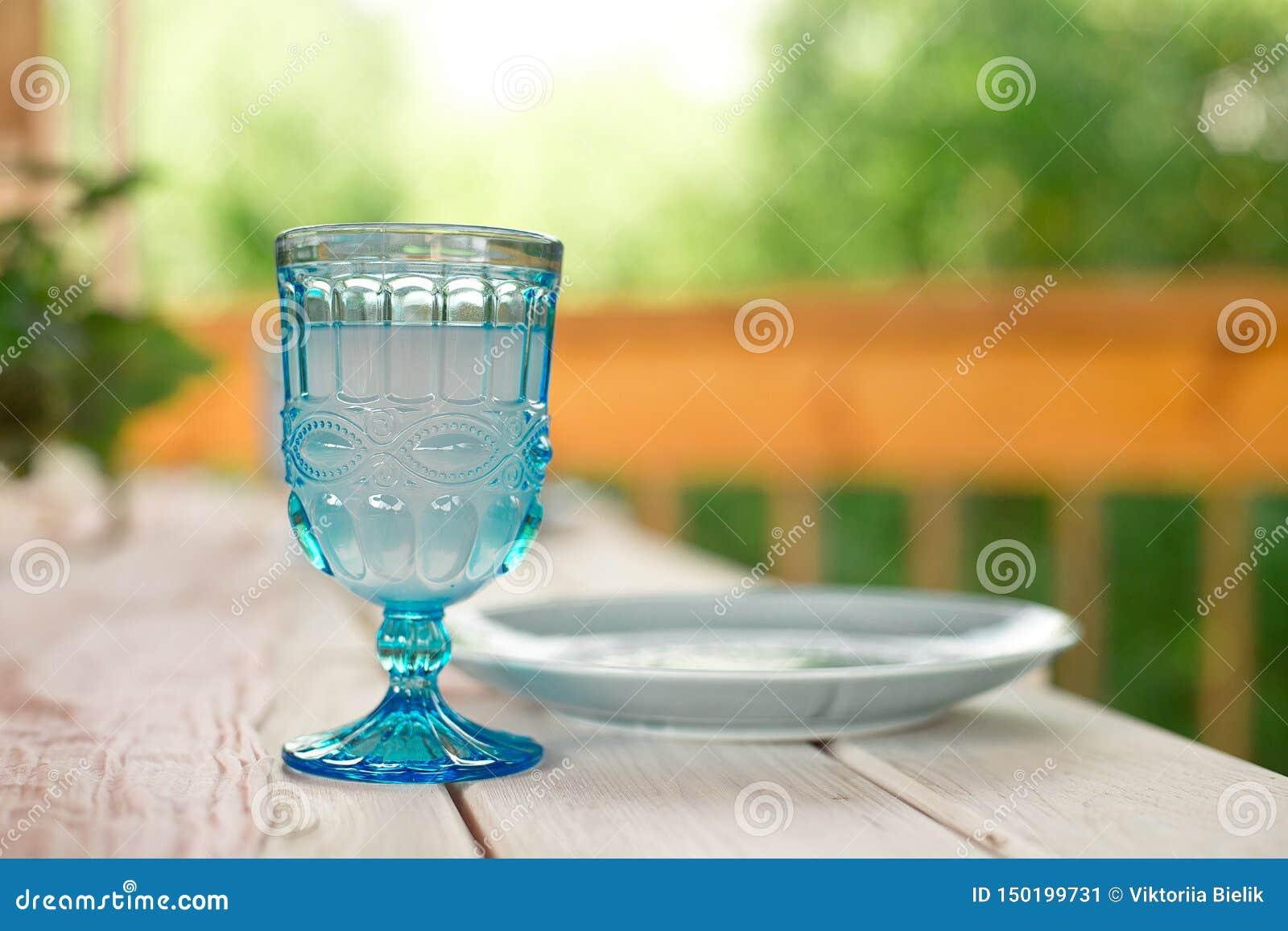 Tabelle für Gäste, verziert mit Kerzen, gedient mit Tischbesteck und Tonware und mit einer blauen Platte der Tischdecke bedeckt u