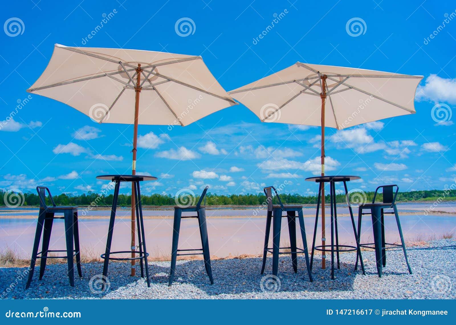 Tabelle und Stühle und Regenschirme nehmen die Fotografie, die oben schaut