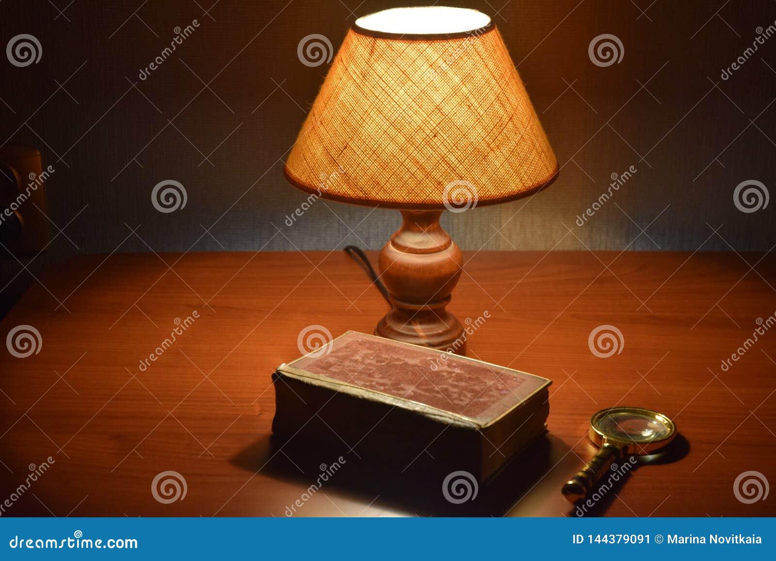 Tabelllampa, gammal bok och förstoringsapparat på skrivbordet
