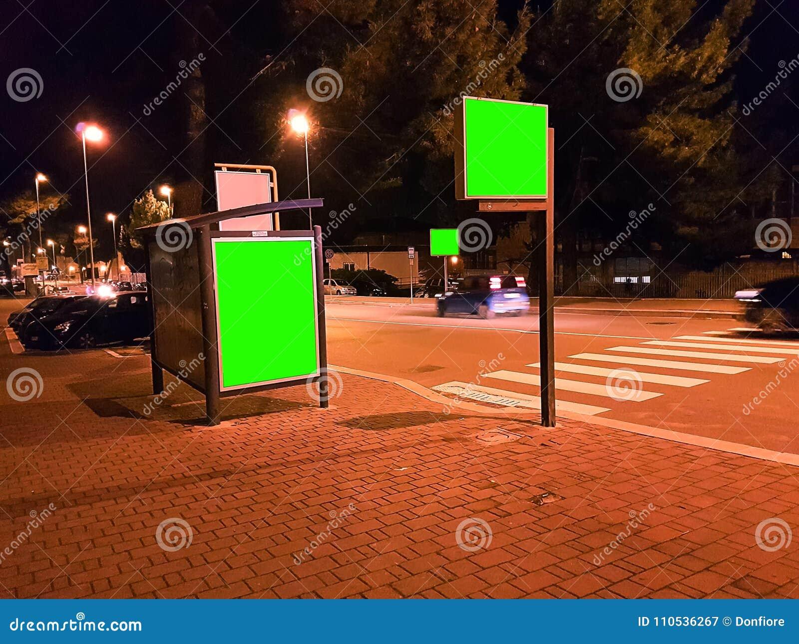 Tabellone per le affissioni con uno schermo di verde di chiave di intensità su una notte della città di traffico