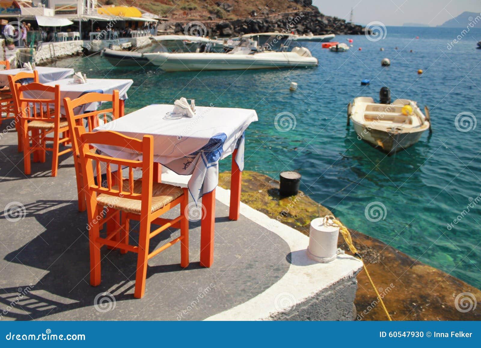 Taberna grega com as cadeiras de madeira alaranjadas pela costa de mar, Grécia,