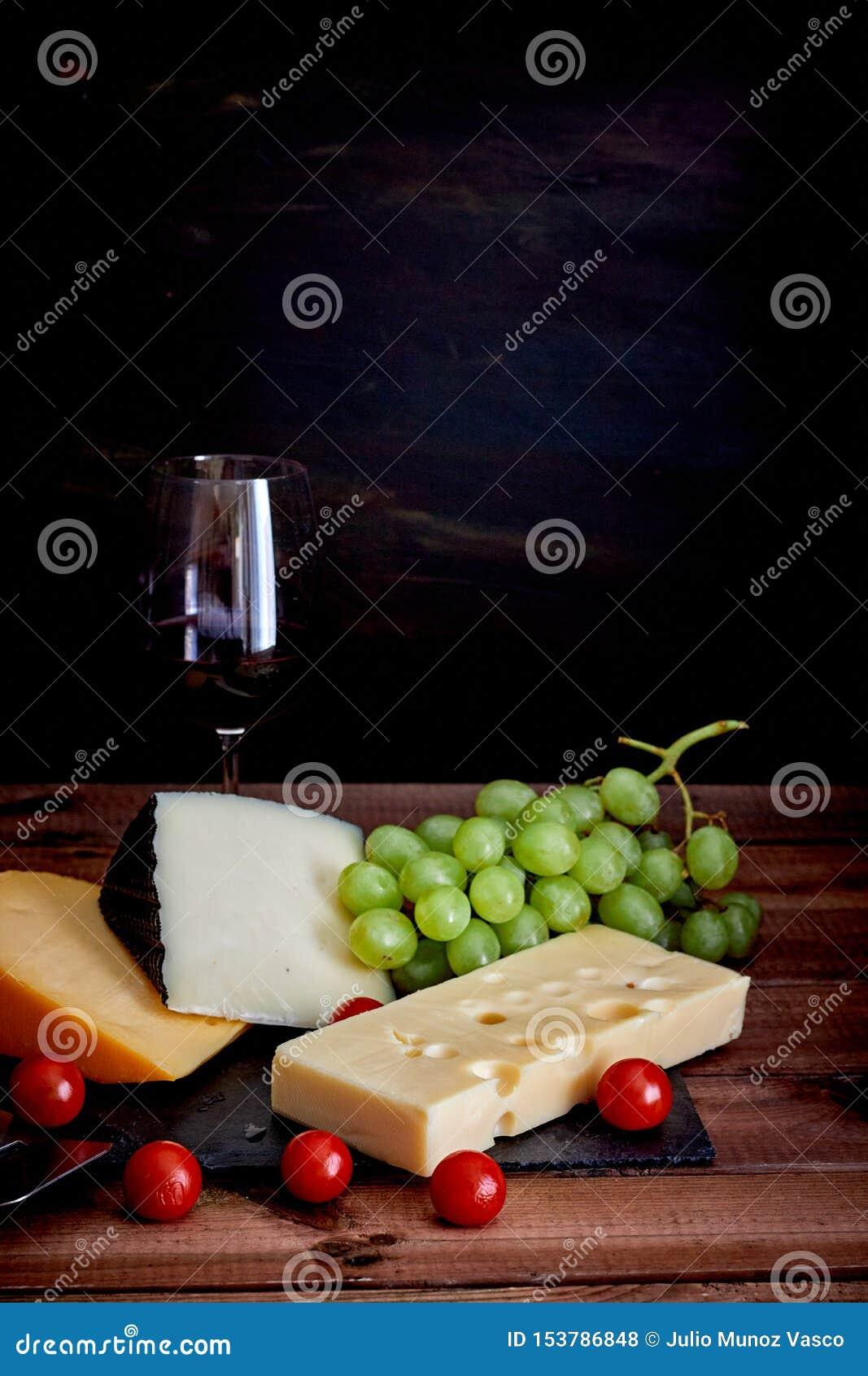 Tabla con diversos quesos y copa de vino en fondo oscuro