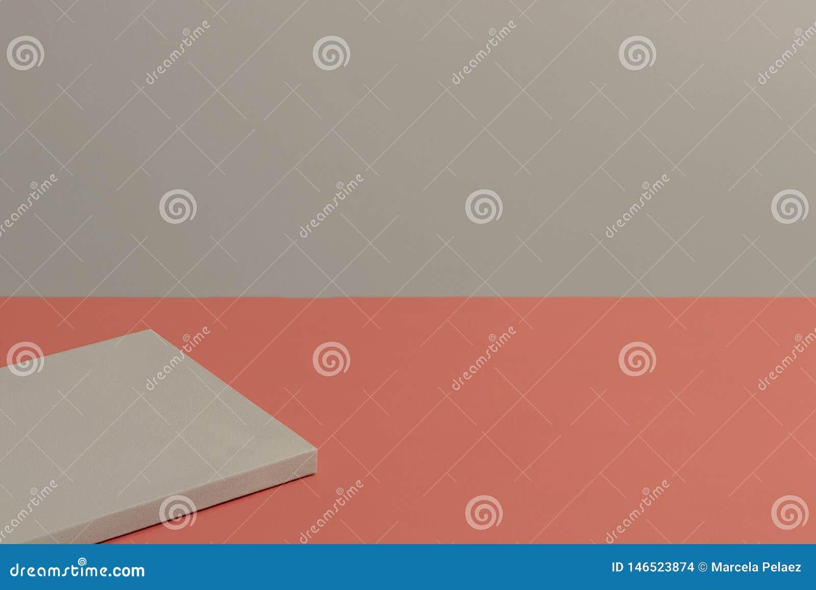 Tabla de color coralina viva con la pared gris y lona en blanco en el top