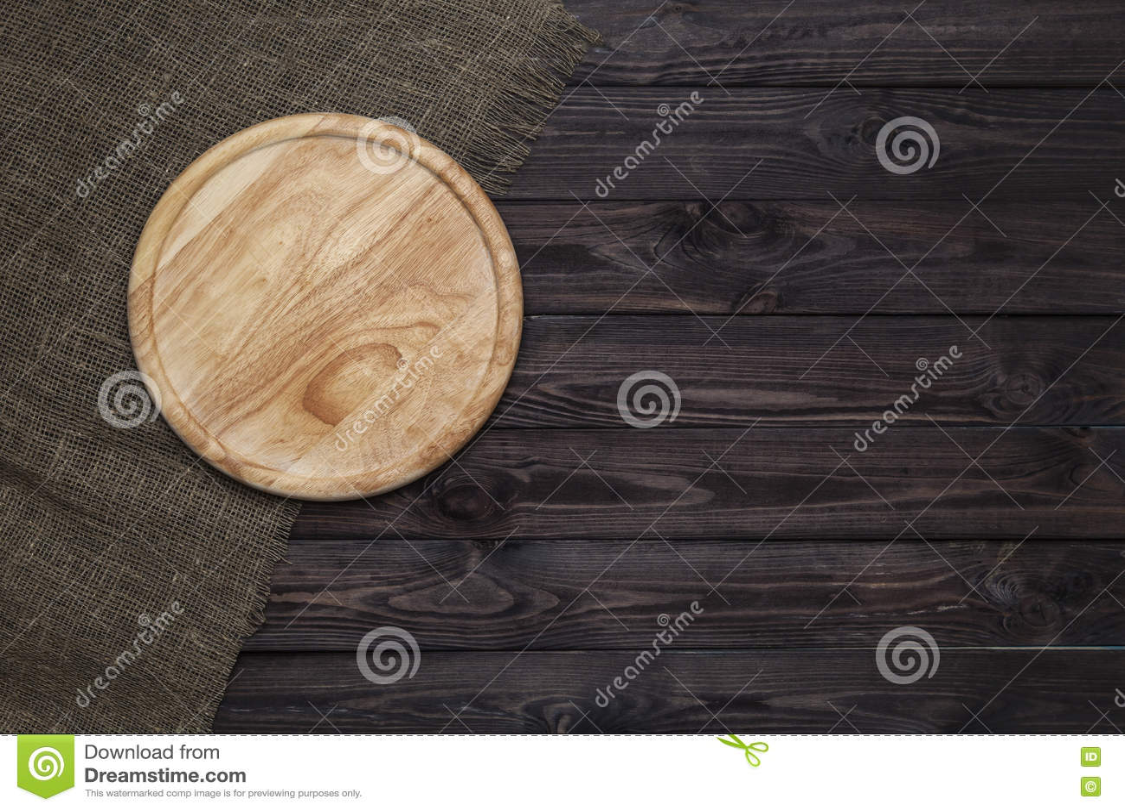 Tabla de cortar redonda en la tabla de madera oscura