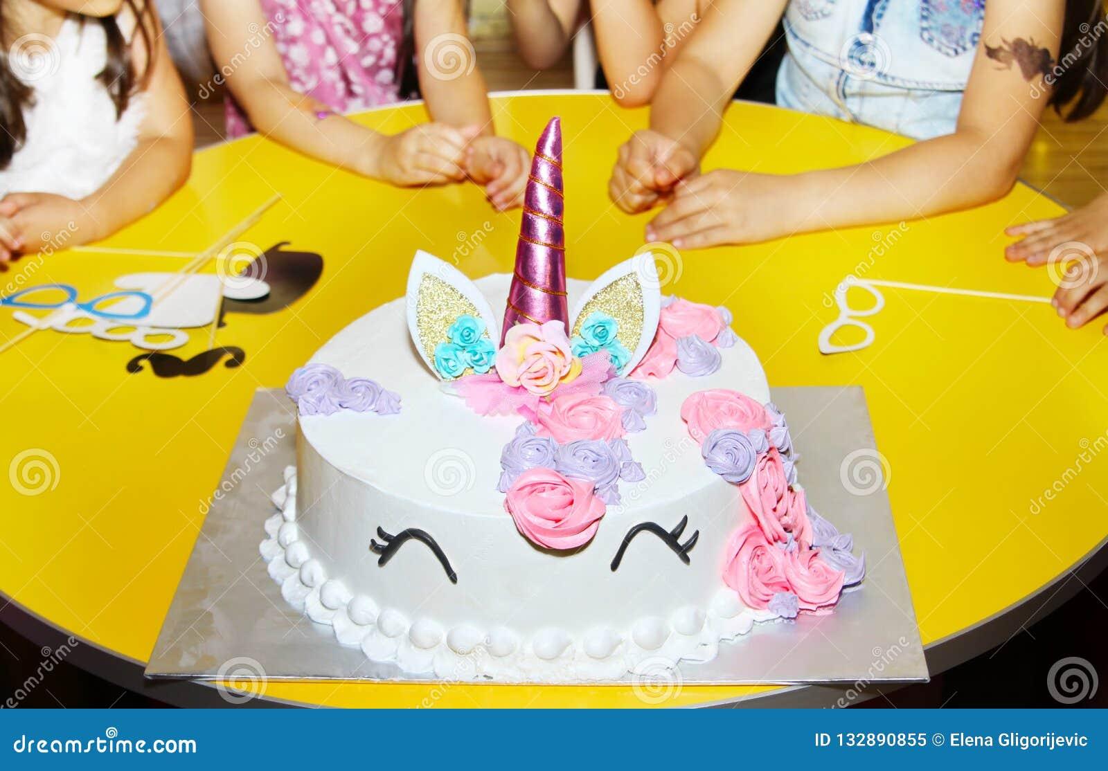 Tabla de la fiesta de cumpleaños de las niñas con la torta del unicornio