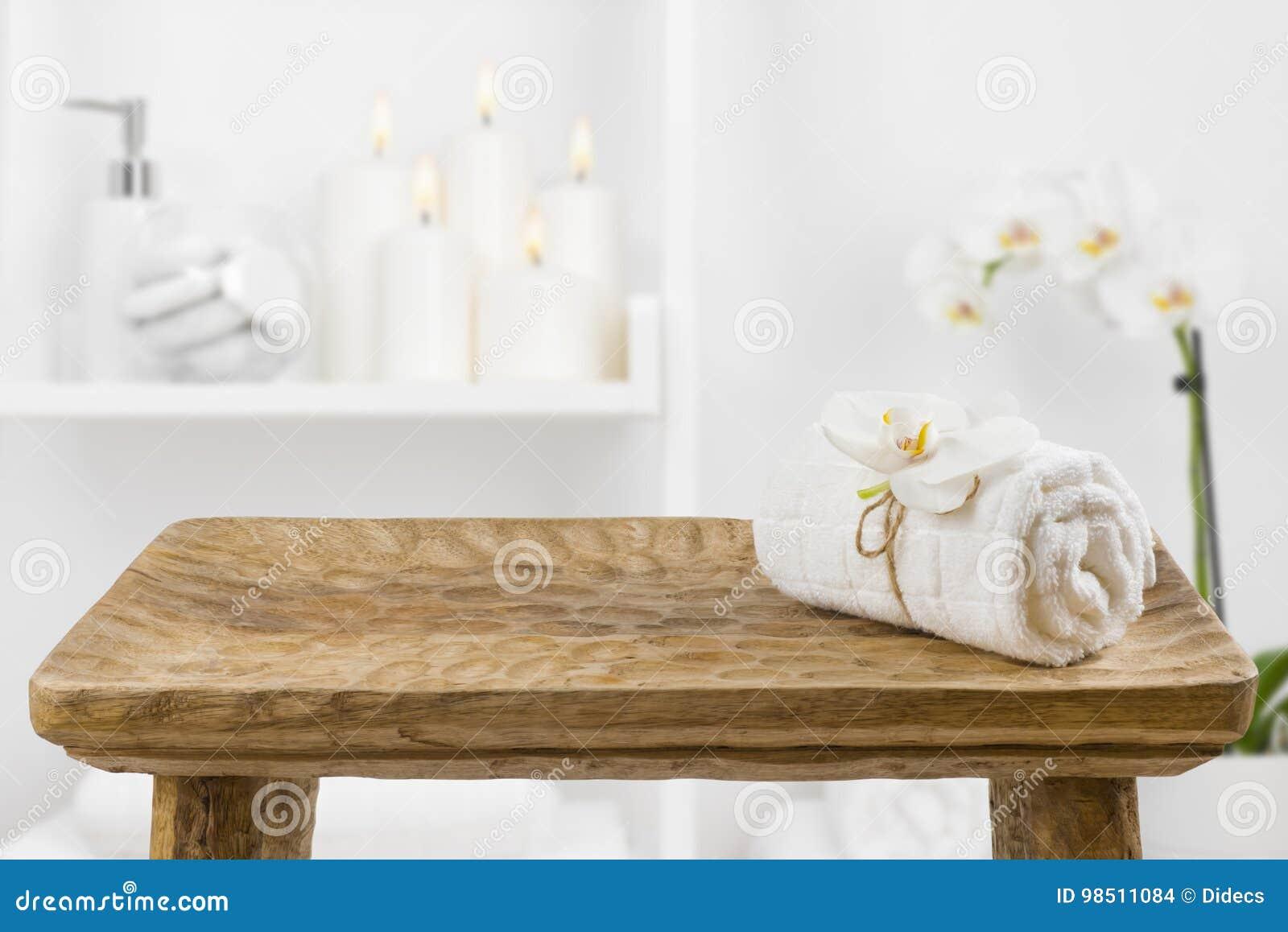 Tabla de madera con la toalla del balneario en fondo borroso del estante del cuarto de baño
